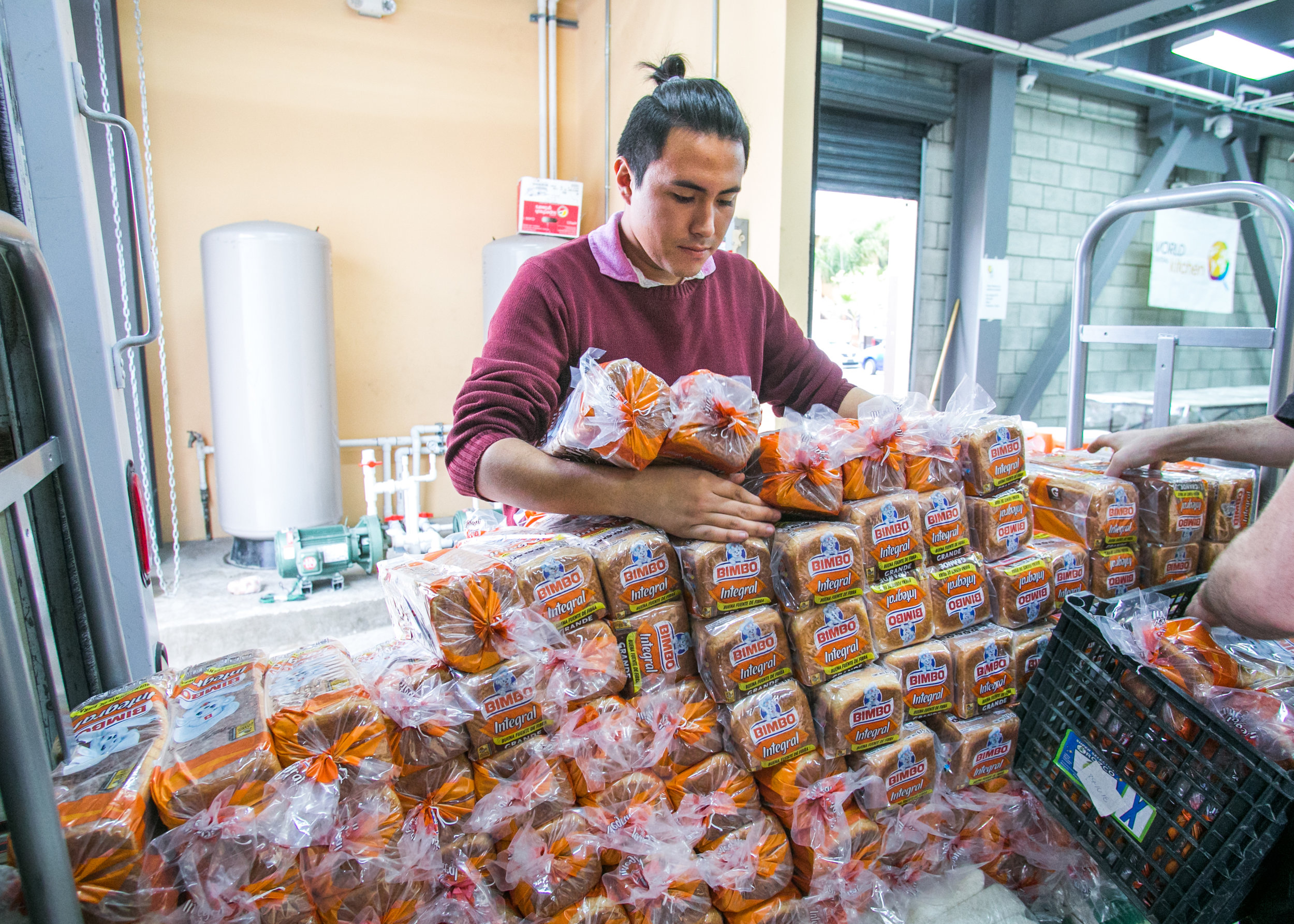 World Central Kitchen volunteer, Ocar Montana, 22, of Tijuana, unloads loafs of bread from a box truck at the WCK headquarters.Three meals a day are provided by local volunteers, churches, or international non-profits.