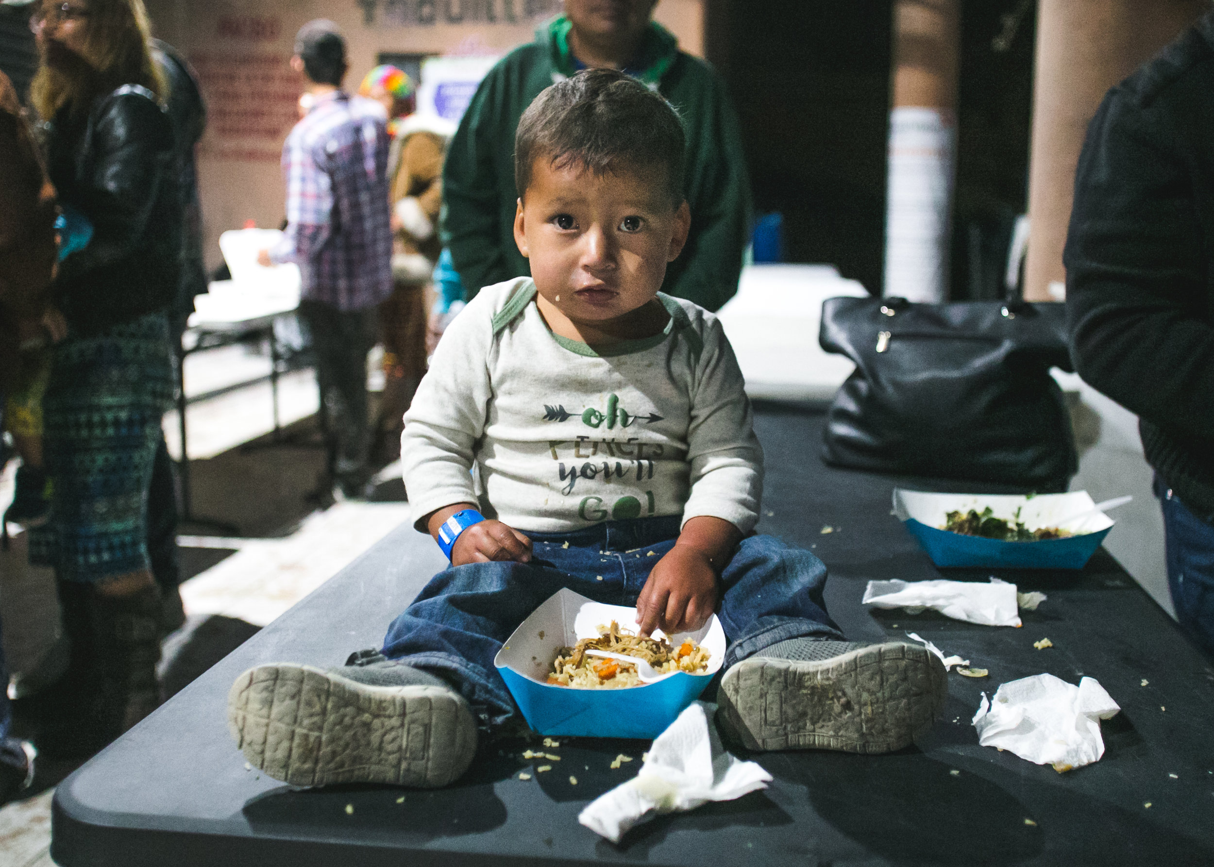 David Zuniga, 2, of Honduras, sits on a dinner table in the Barretal migrant camp located 20 minutes outside of Tijuana. Three meals a day are provided by local volunteers, churches, or international non-profits. David is covered by a dinner served moments earlier by World Central Kitchen - Chef Jose Andres's global hunger non-profit. The group of volunteers has been serving 1,200-1,400 meals two time a day since December 5th 2018.