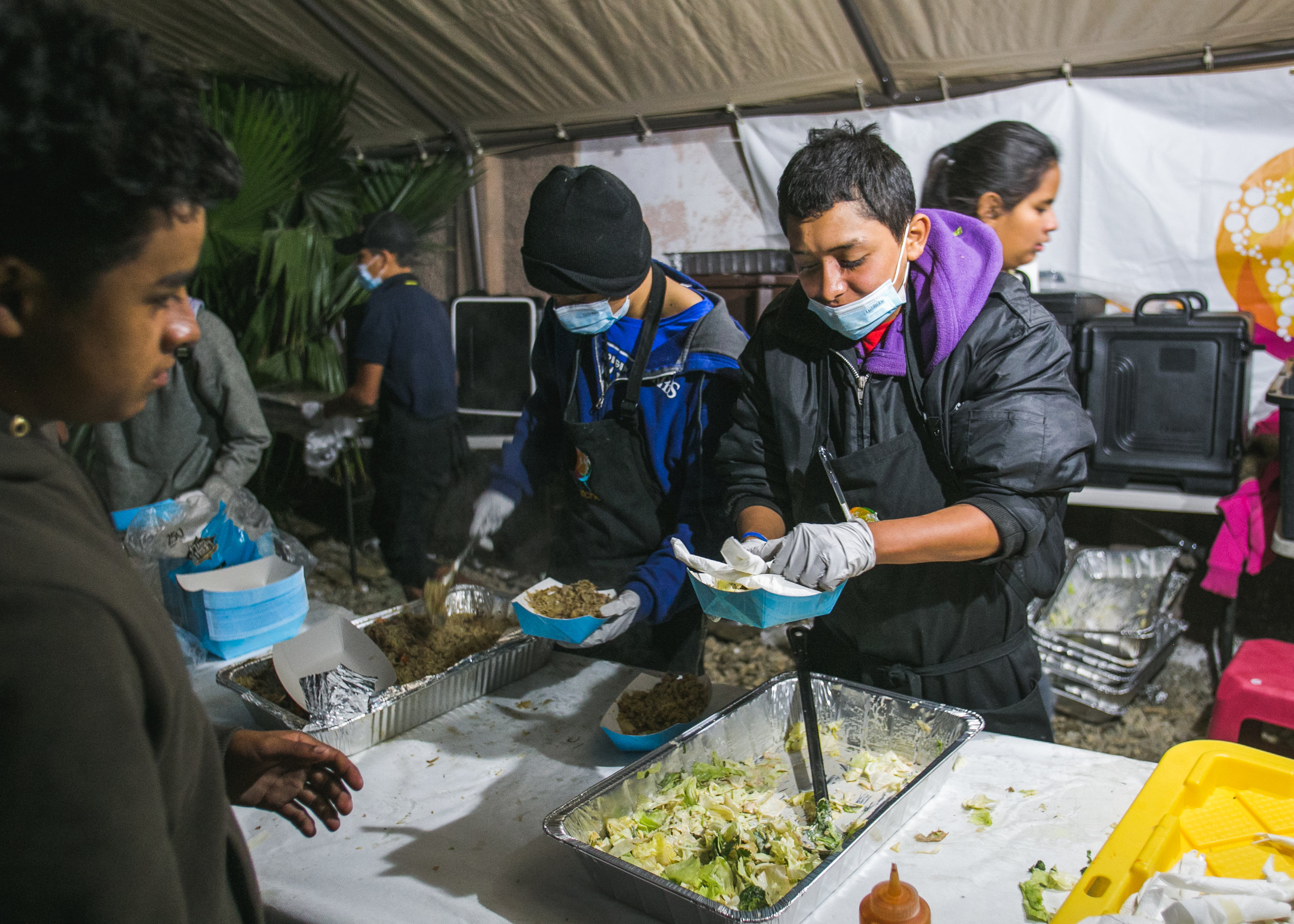 A volunteer serves dinner to over 1,500 refugees at the Barretal refugee compound. Each day, 5-6 children from the camp would assist World Central Kitchen with serving lunch. The goal of the program surrounds creating a sustainable refugee-operated kitchen in Tijuana to serve for months (or even years) to come. The recent influx in caravan activity has drawn mass media attention - but contrary to popular belief - refugees from Central America have been arriving in Tijuana for over a decade.