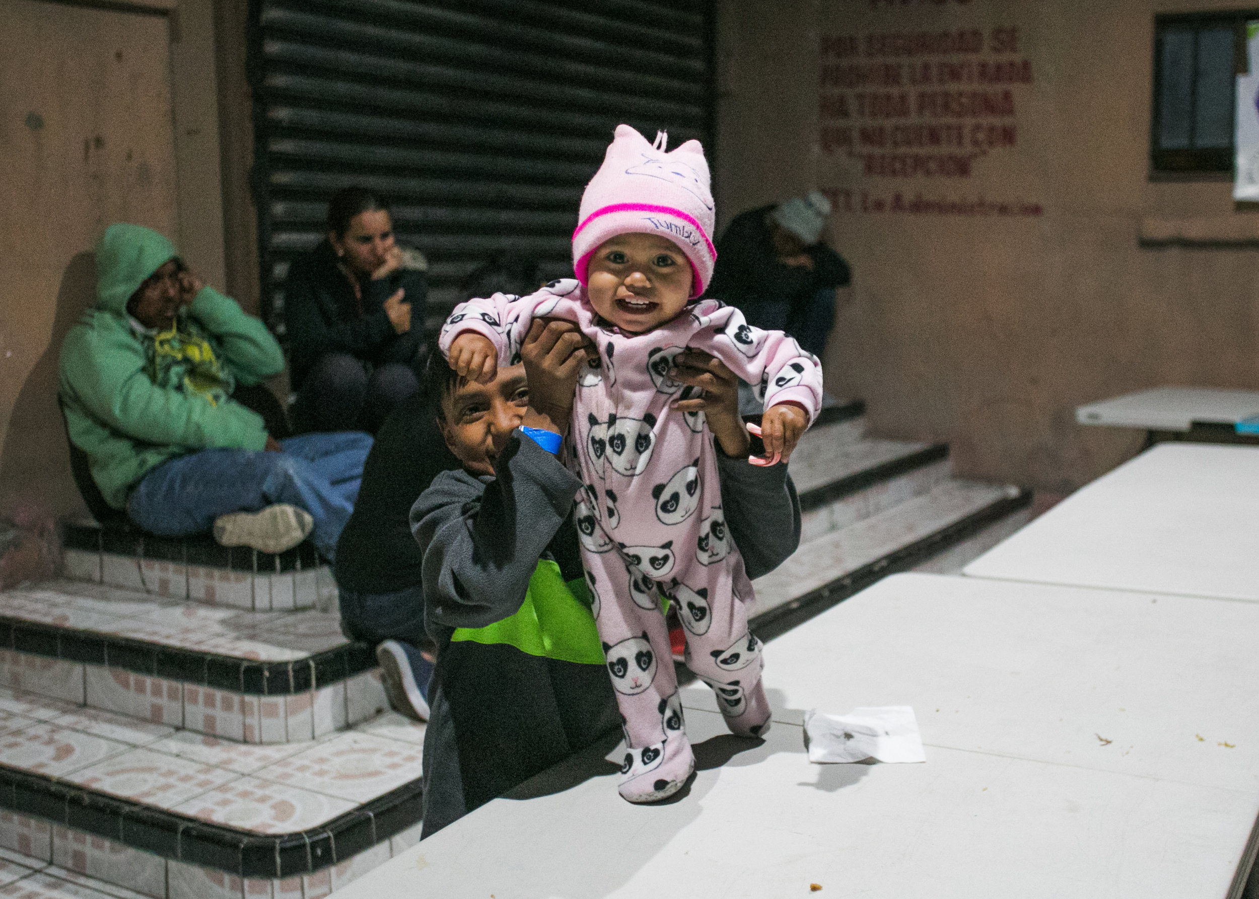 Siblings play on the dinner tables of Barretal refugee camp in Tijuana, Mexico.