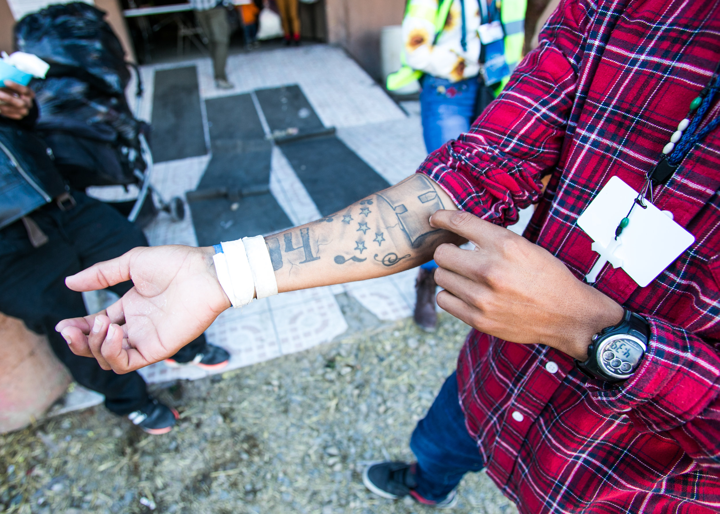 """Kevin Hernandez, 19, of Honduras, rolls up his sleeve to show off the tattoos he got several years prior. The numbers hidden by the camp passes on his wrist is the area code of his family home in Honduras. The """"H"""" directly above it (on his forearm) represents pride for his home country. Despite the gang turmoil tearing his neighborhood apart - he says he """"misses Honduras"""", and """"wishes he could return to be with his mother""""."""