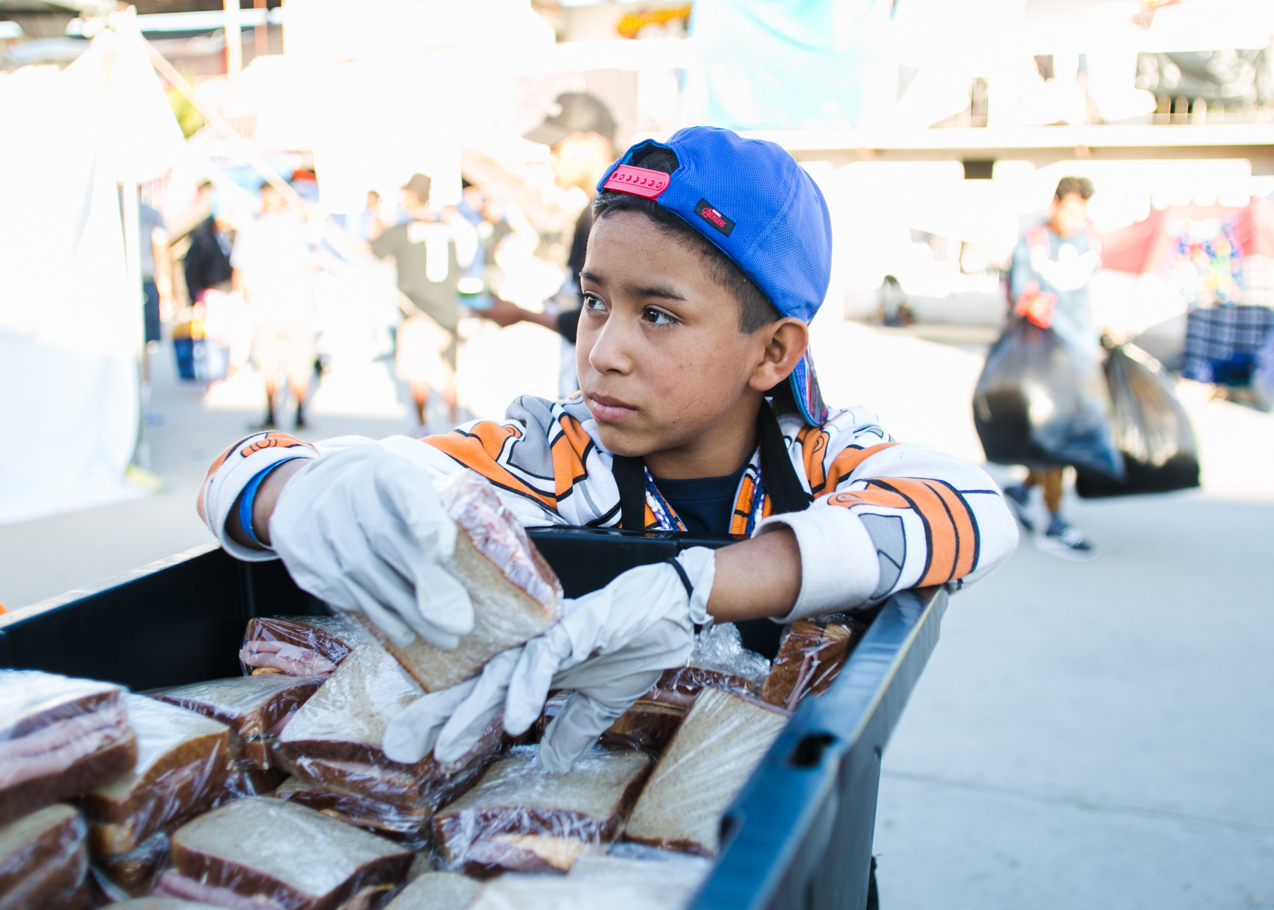 A Honduran refugee gives out sandwiches prepared by World Central Kitchen in the Barretal refugee camp located just outside of Tijuana, Mexico.