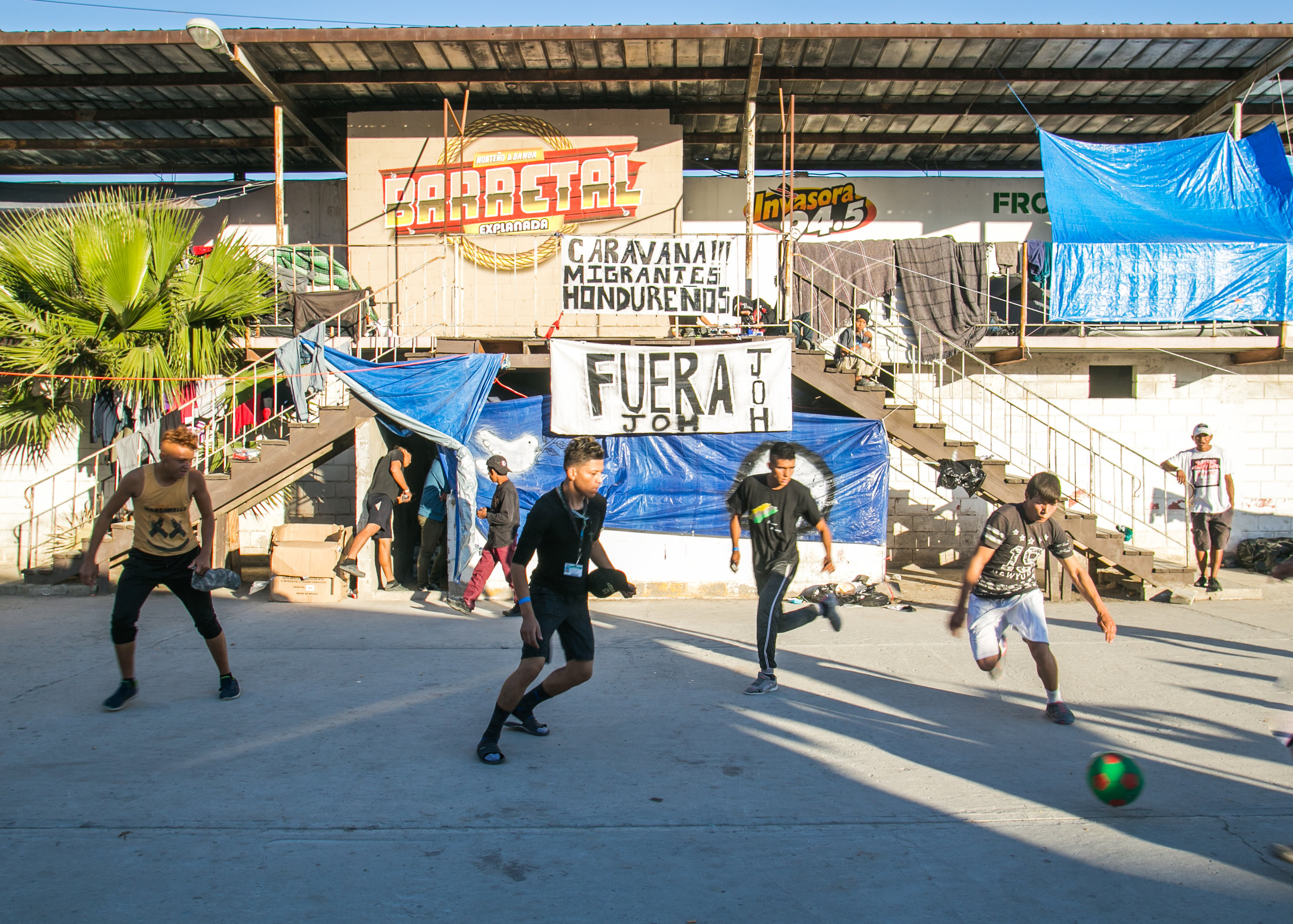 Refugees play soccer in the single male section of the Barretal border camp located just outside of Tijuana, Mexico.