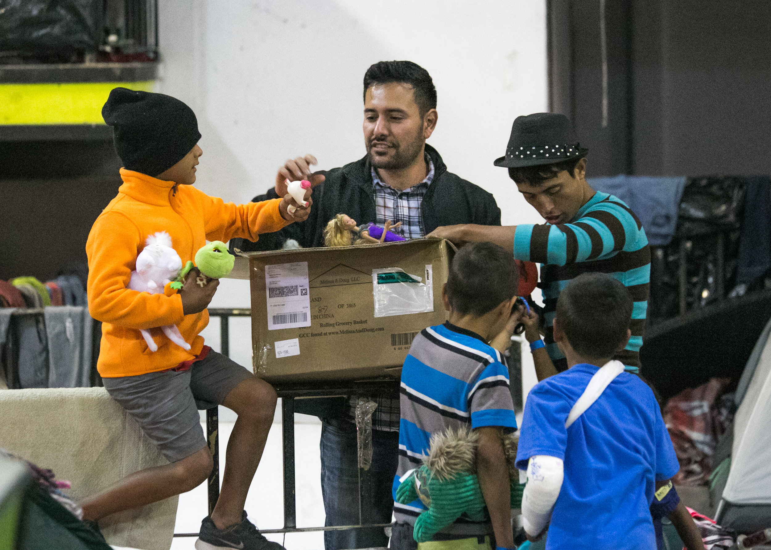 Volunteer, Rodrigo Rodriguez, of San Diego, hands out toys to refugee children in the Barretal camp located in Tijuana, Mexico. Rodrigo also purchased a washer and dryer for the facility.
