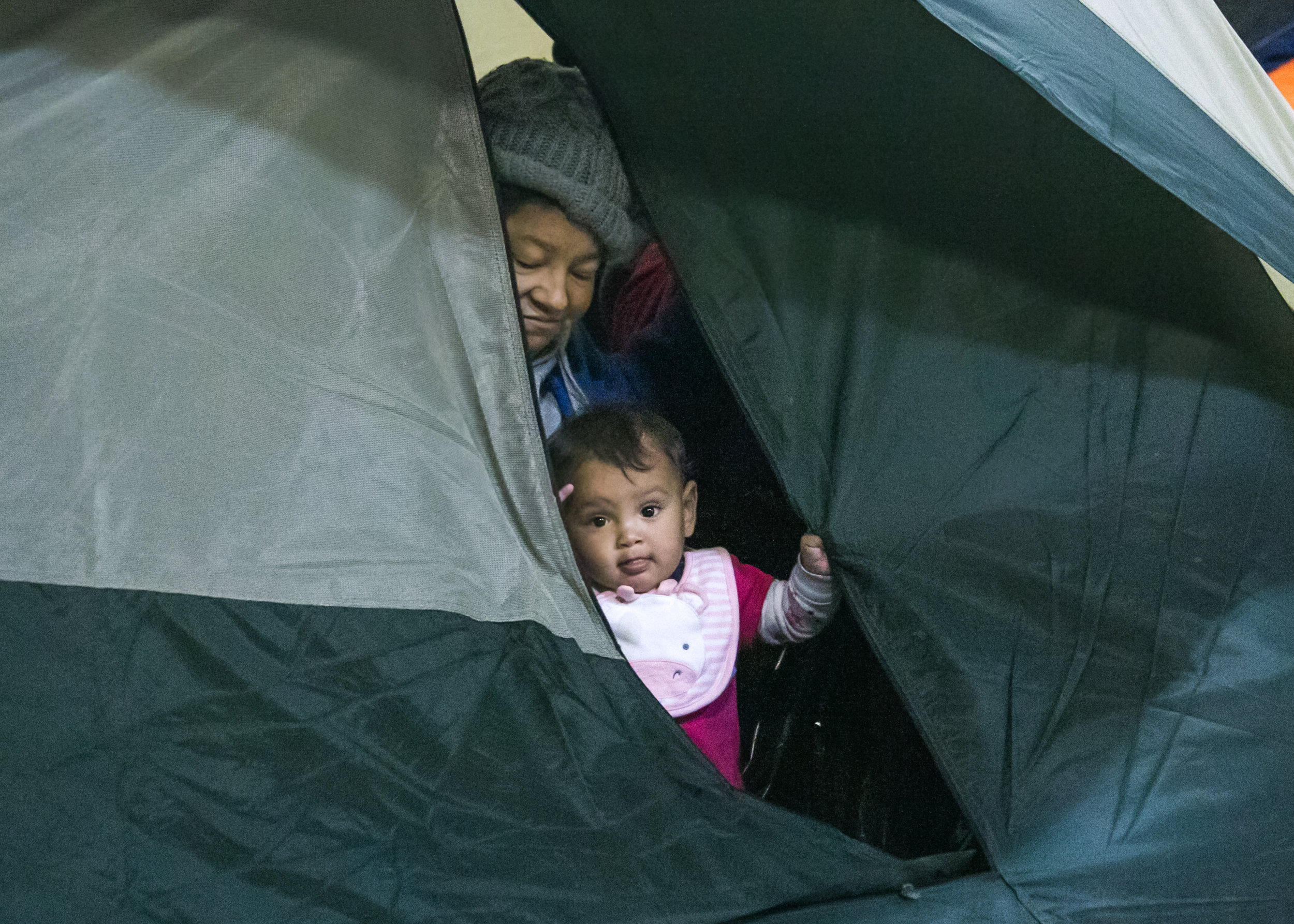 A child and her grandmother peer out of their tent to watch children playing outside. The Barretal camp now houses between 1,500 and 2,000 migrants - with 30-40 leaving and coming each day.