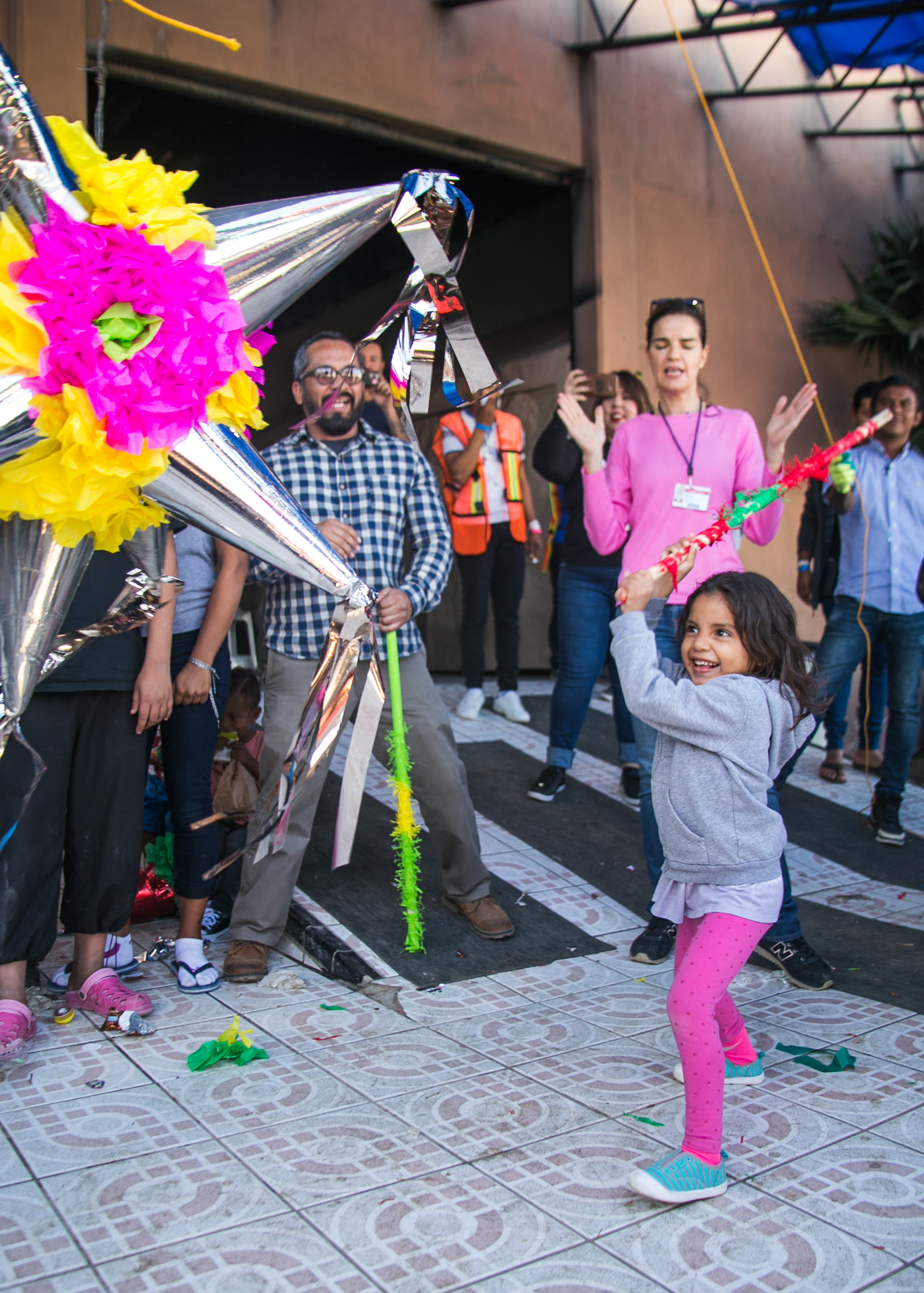 A child strikes a piñata with joy after six were donated for the many children occupying the Barre Tal refugee camp in Tijuana.