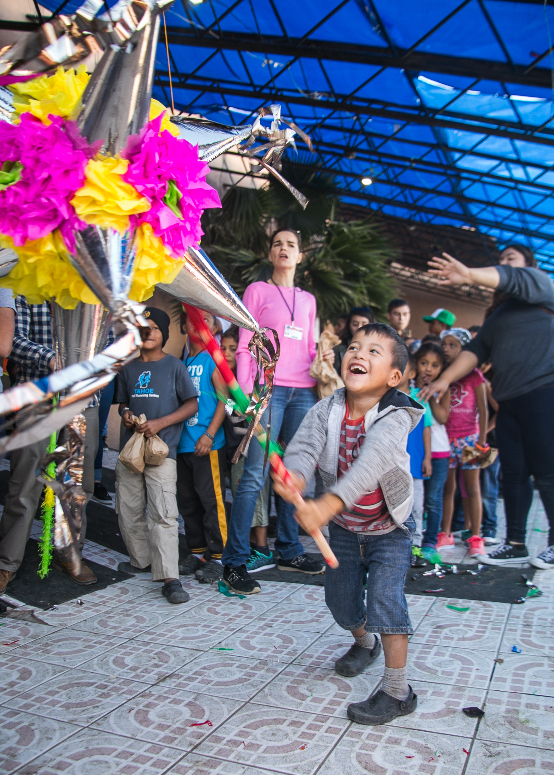 A child strikes a pinnate with joy after six were donated for the many children occupying the Barretal refugee camp in Tijuana.