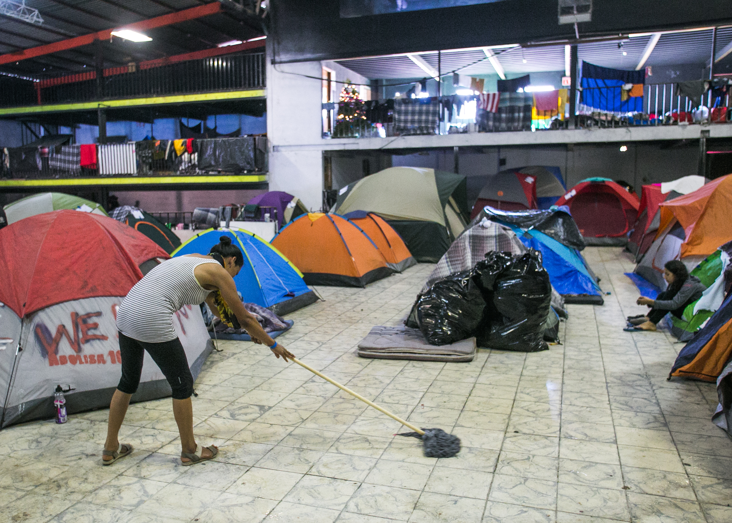A refugee cleans the floors of the family section inside the Barretal compound located in Tijuana. Mexico.