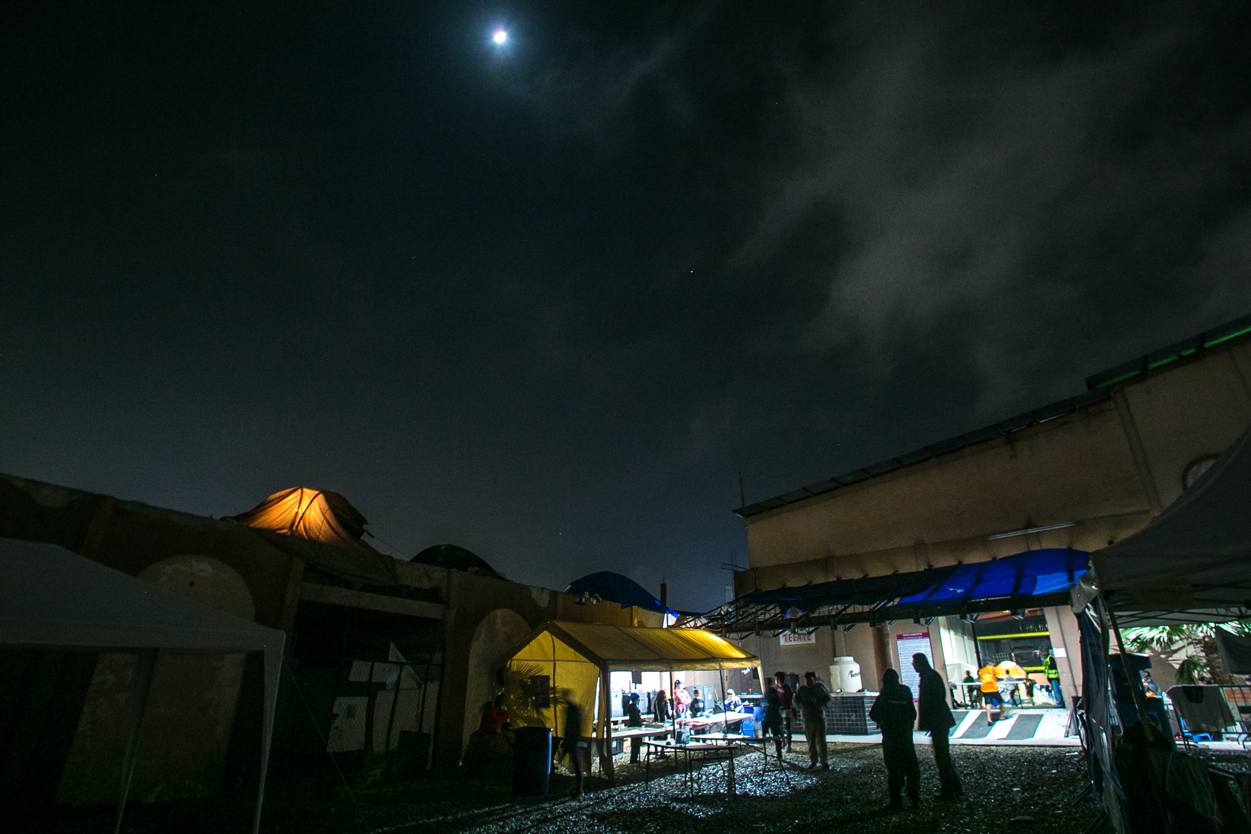 An illuminated tent is silhouetted against the night sky in the Barretal refugee camp outside of Tijuana, Mexico.