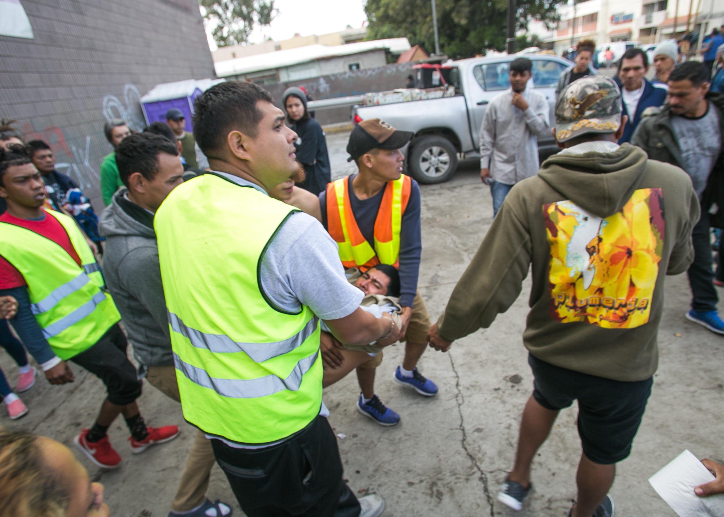 A man is carried out of the El Chinchetta refugee compound in Central Tijuana. He began seizing and vomiting due to a lack of medication according to responders on scene. Medical services were suspended in the facility several days prior in an effort to close the compound. Care from independent non-profits slipping past the police-guarded entrances is all that remain. Recent complaints from community members in Central Tijuana have lead to the government relocating migrant camps to low-income suburban communities on the outskirts of Tijuana.