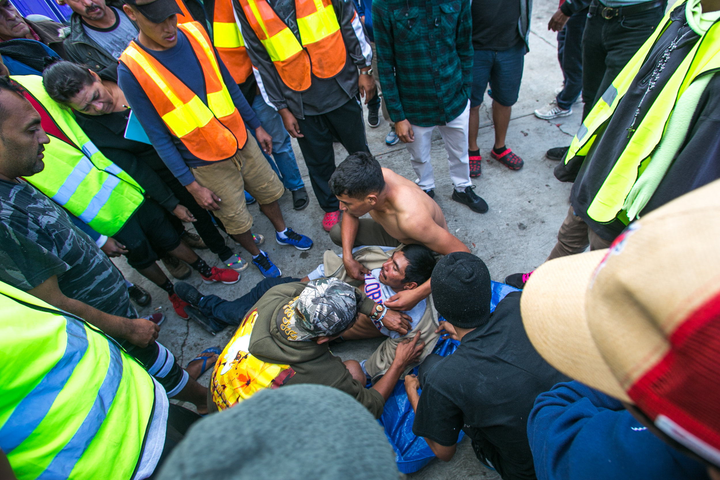 A man receives rudimentary medical attention from other migrants while waiting for emergency services. He began seizing and vomiting due to a lack of medication according to responders on scene. Medical services were suspended in the facility several days prior in an effort to close the compound. Care from independent non-profits slipping past the police-guarded entrances is all that remain. Recent complaints from community members in Central Tijuana have lead to the government relocating migrant camps to low-income suburban communities on the outskirts of Tijuana.