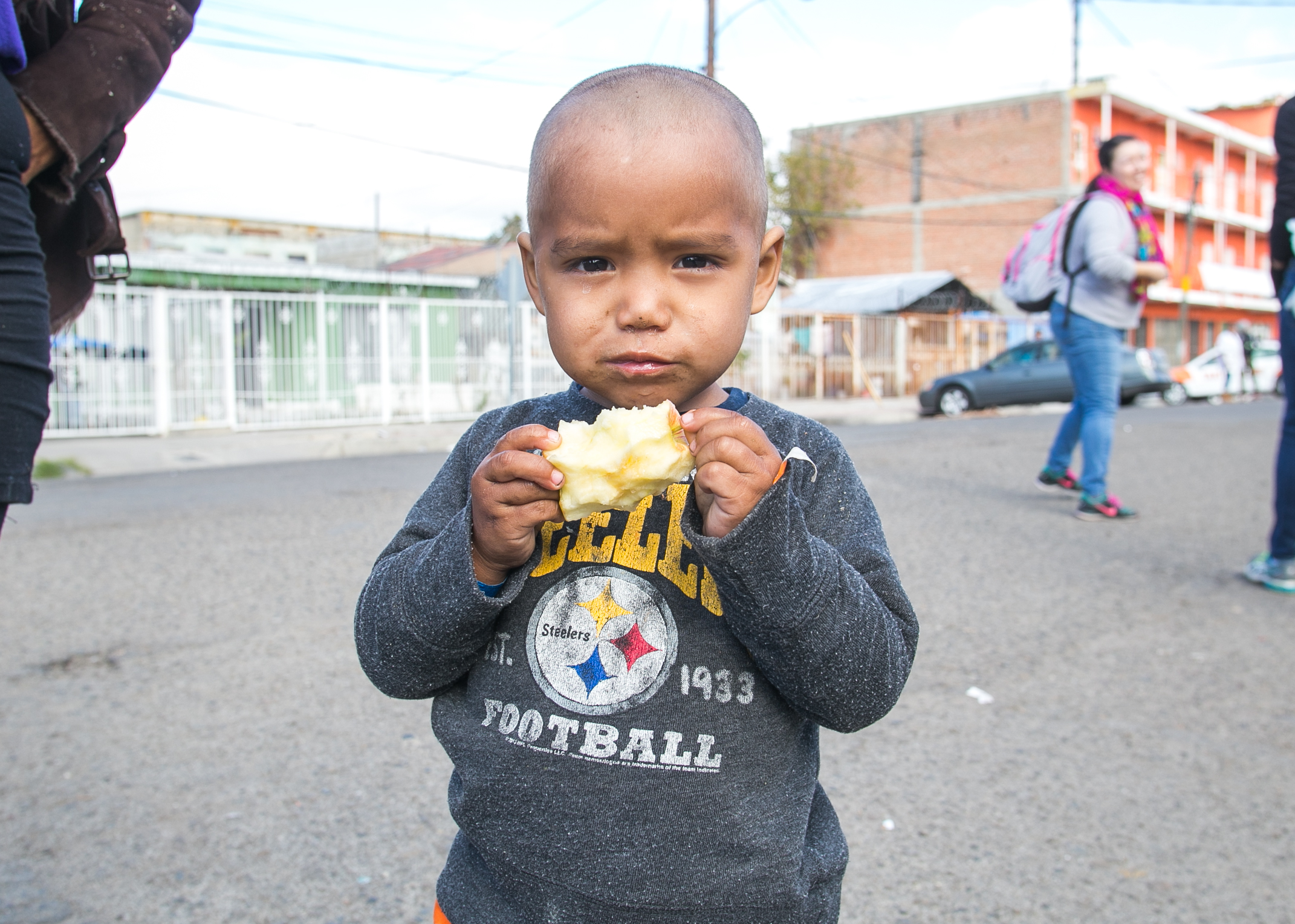 A young Honduran refugee sporting a Steelers sweatshirt eats an apple provided by World Central Kitchen at the El Chinchetta refugee compound in Central Tijuana.