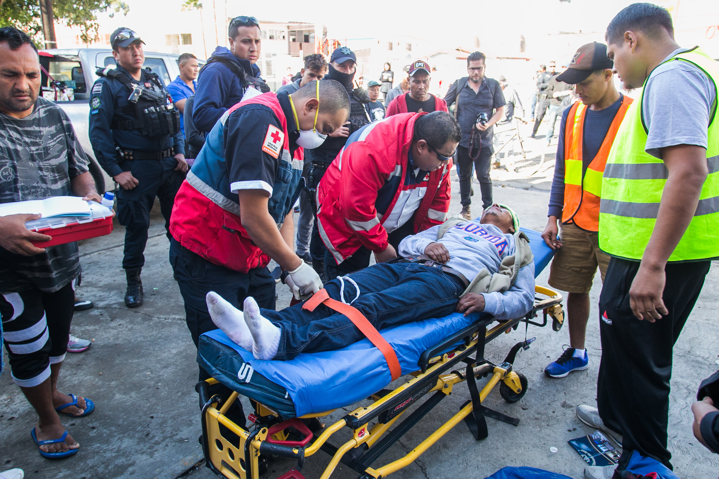 A man receives medical attention from emergency services after waiting for over 25 minutes. He began seizing and vomiting due to a lack of medication according to emergency responders on scene. Medical services were suspended in the facility several days prior in an effort to close the compound. Care from independent non-profits slipping past the police-guarded entrances is all that remain. Recent complaints from community members in Central Tijuana have lead to the government relocating migrant camps to low-income suburban communities on the outskirts of Tijuana.
