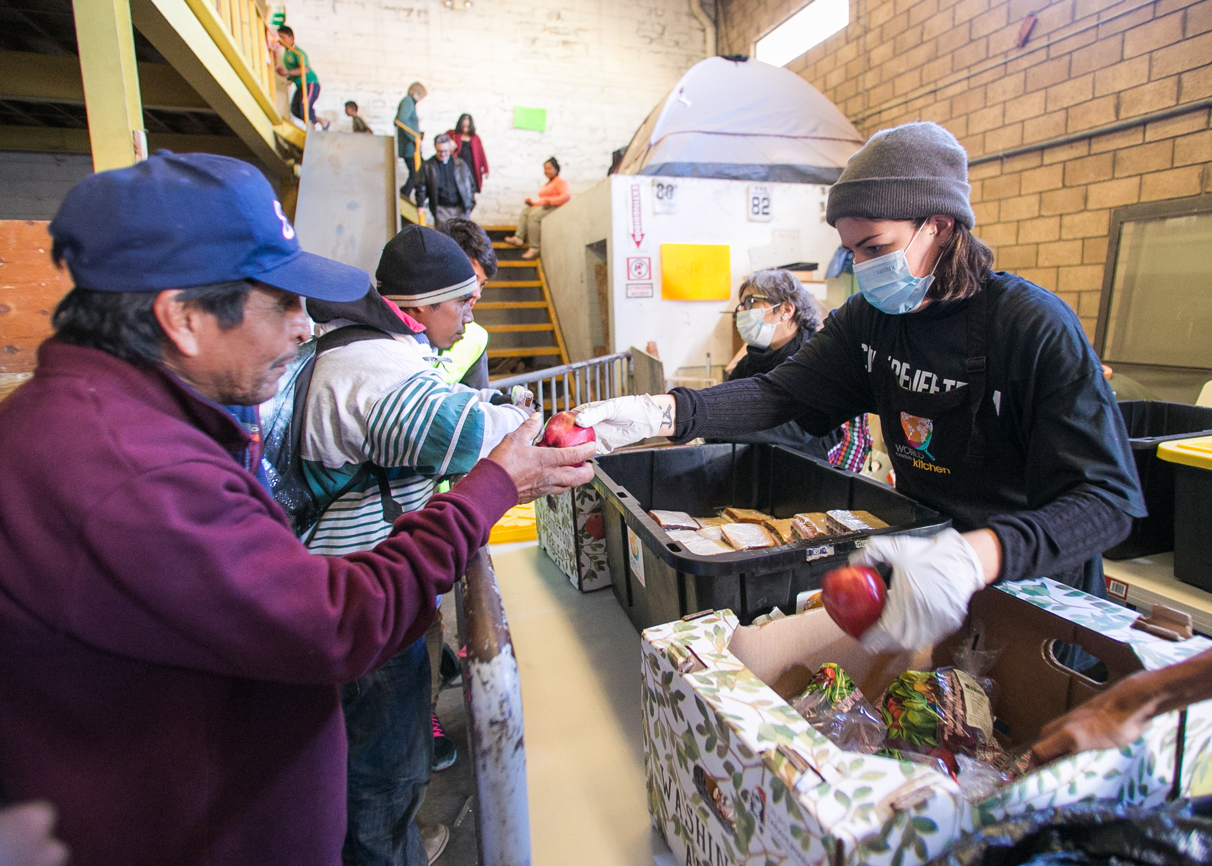 A World Central Kitchen volunteer serves refugees in the El Chinchetta compound located in Central Tijuana.