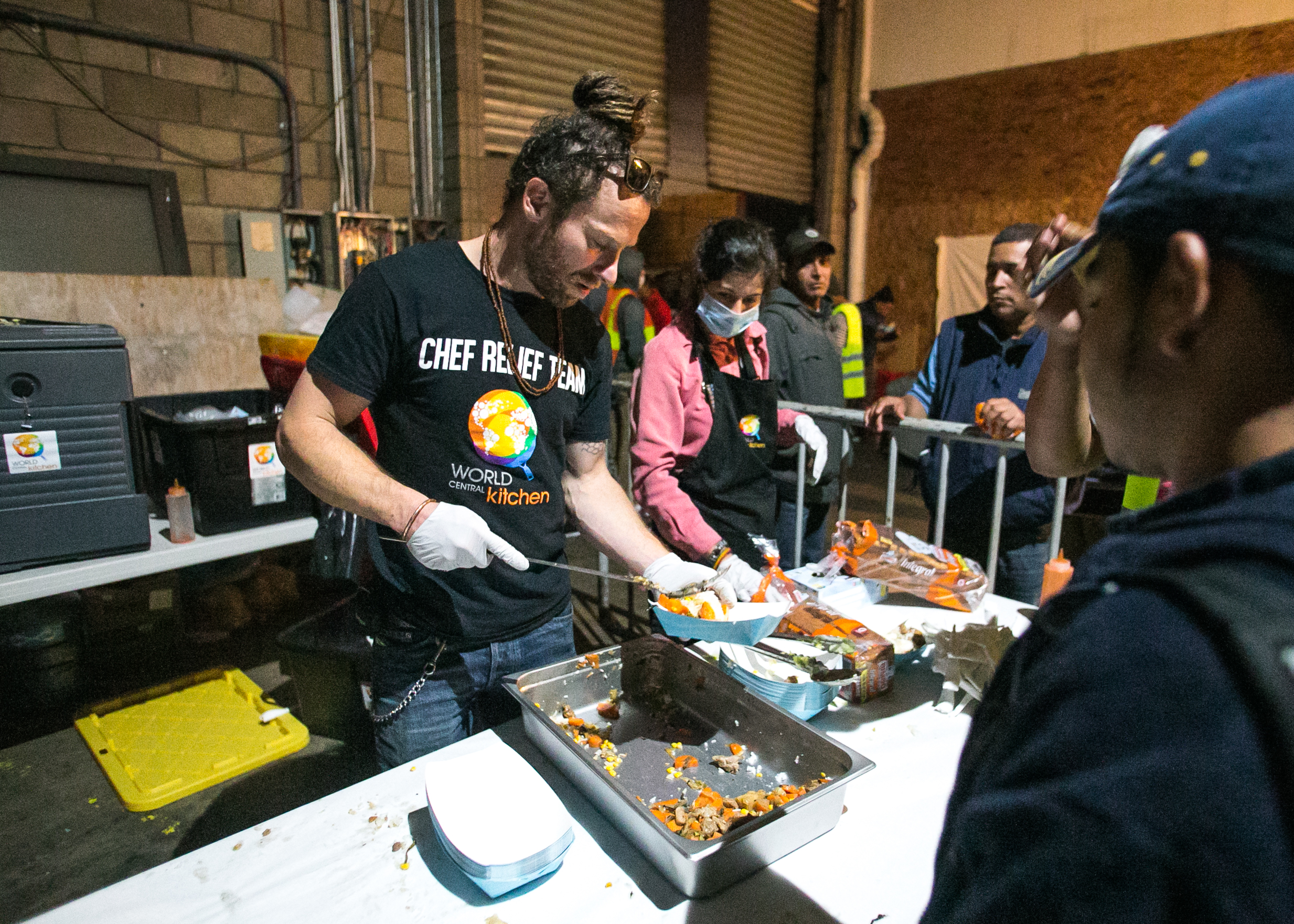 Project Leader, Sam Bloch, serves dinner to refugees living in the El Chinchetta compound in Central Tijuana.