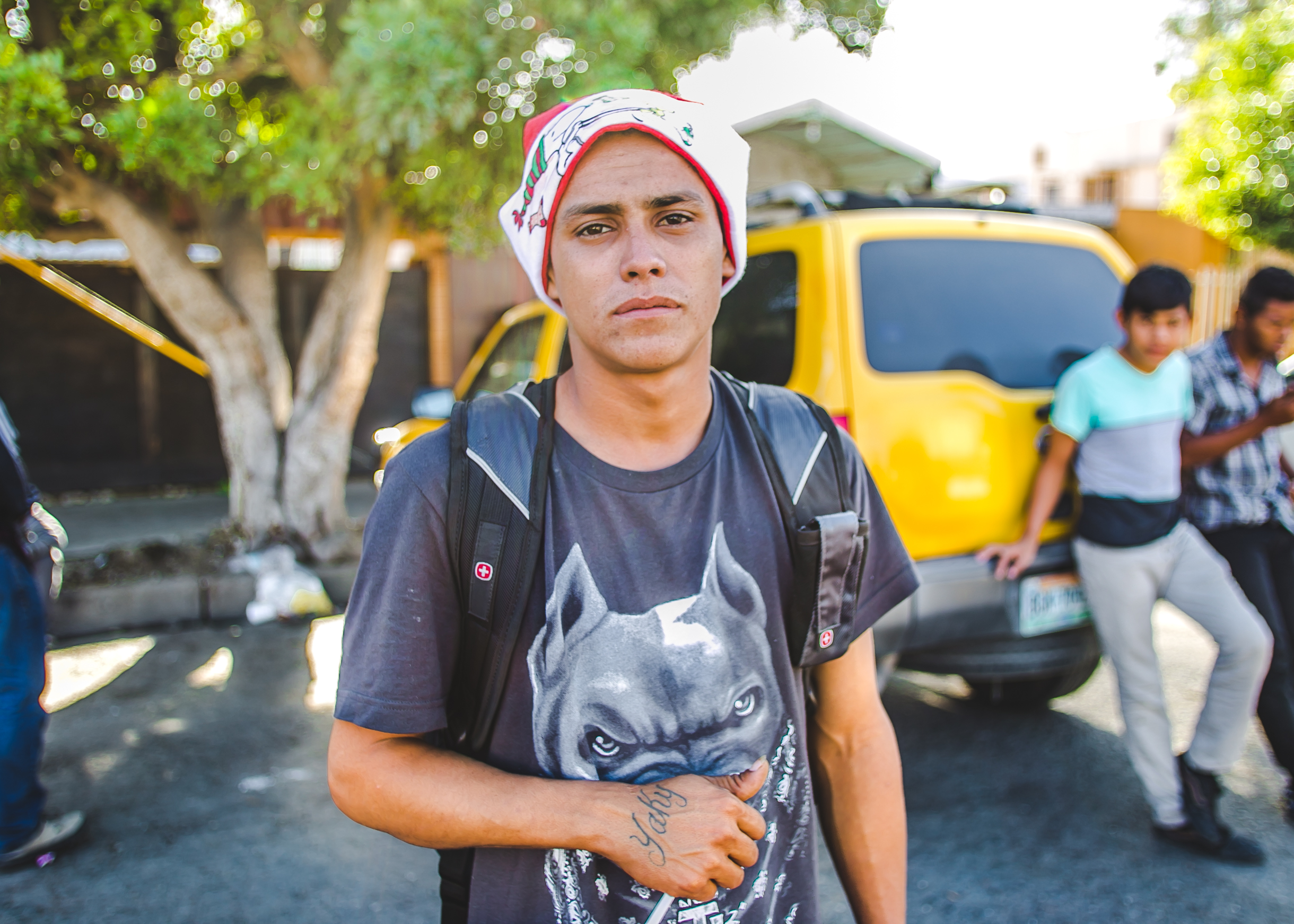 Heraldo Enrique, 19, of Honduras, stands wearing a Santa hat outside the El Chinchetta compound in Central Tijuana. Heraldo left Honduras to escape the pressure of joining a gang. He has been on the road alone for two months
