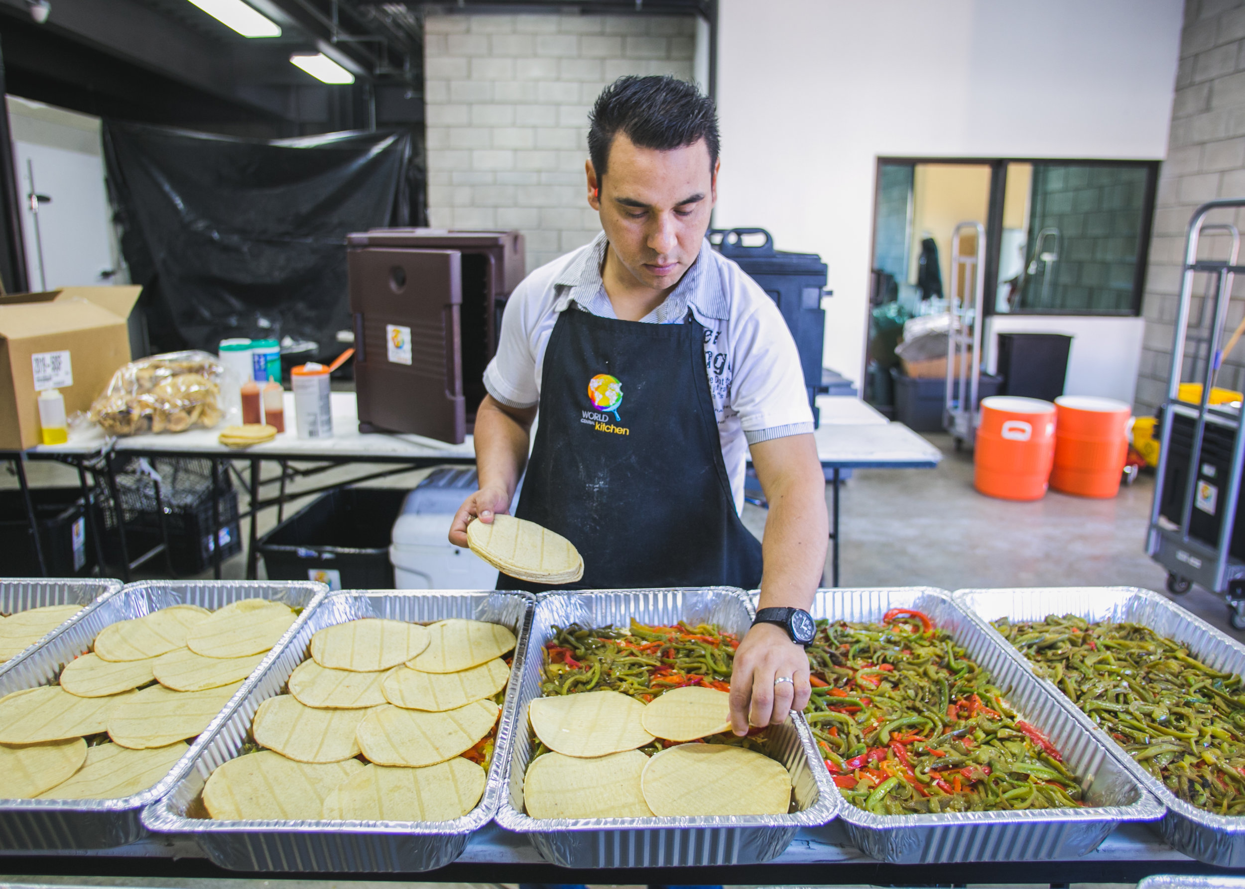 Tijuana pastor and volunteer Leopold Perez helps make dinner for the Barretal refugee camp in the World Central Kitchen Headquarters.