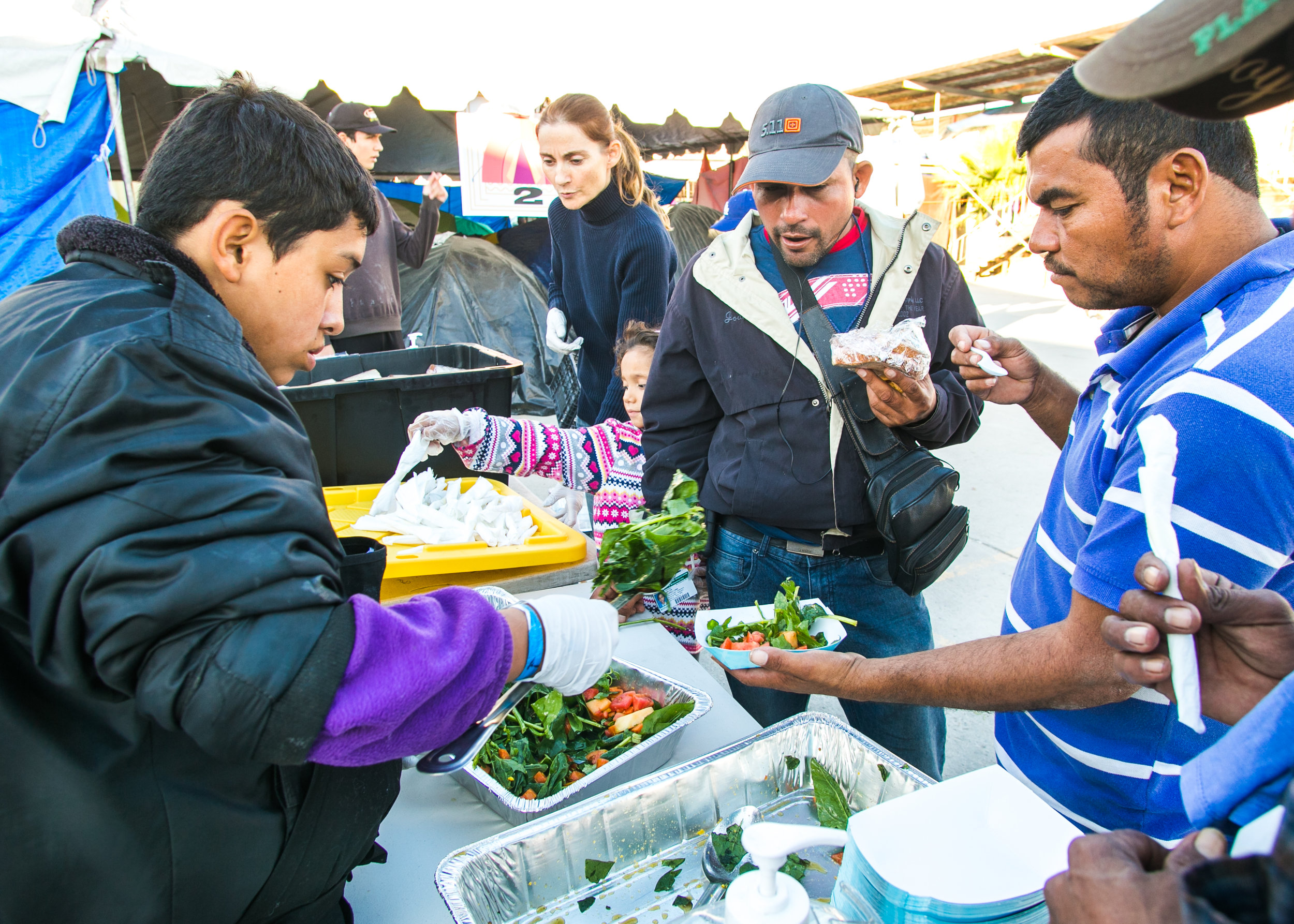 A volunteer serves lunch to over 1,500 refugees at the Barretal refugee compound. Each day, 5-6 children from the camp would assist World Central Kitchen with serving lunch. The goal of the program surrounds creating a sustainable refugee-operated kitchen in Tijuana to serve for months (or even years) to come. The recent influx in caravan activity has drawn mass media attention - but contrary to popular belief - refugees from Central America have been arriving in Tijuana for over a decade.