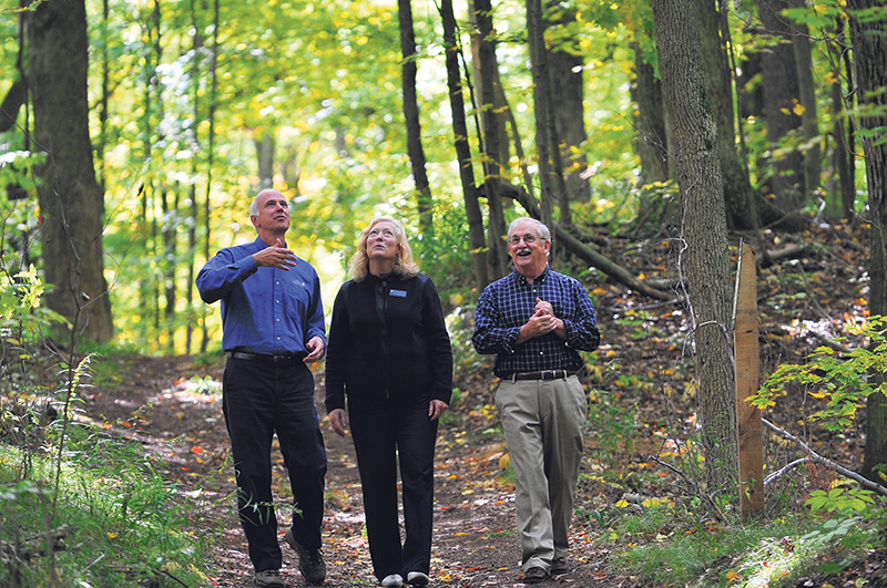 Paul Smith (right) takes a walk through the forest he transferred to NCC, with Karen Clarke-Whistler, chief environment officer of TD Bank Group, and John Lounds, NCC president and CEO. Simon Wilson