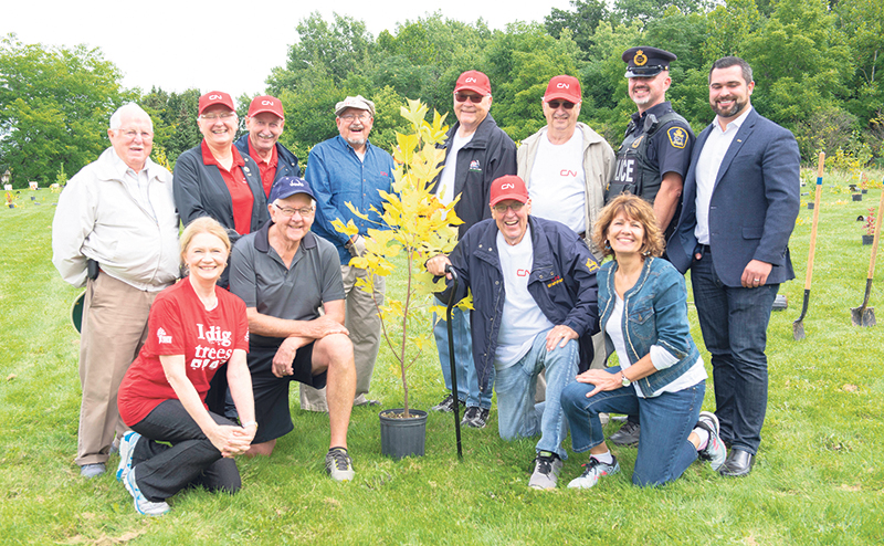 CN pensioners and employees are joined at a CN EcoConnexions tree-planting event on September 8, 2018, by London MP Kate Young (kneeling on left) and London City Councillor Anna Hopkins (kneeling on right). CN