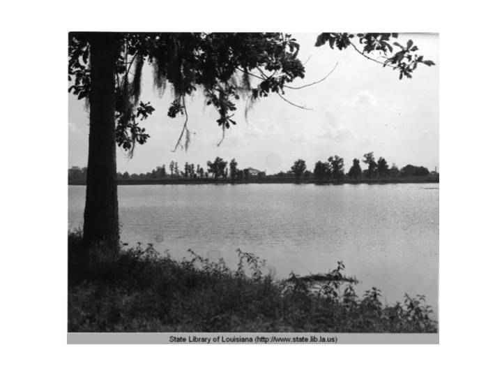 "A spot on the lake. In the distance is the John M. Parker Agricultural Coliseum, also known as the ""Cow Palace."""