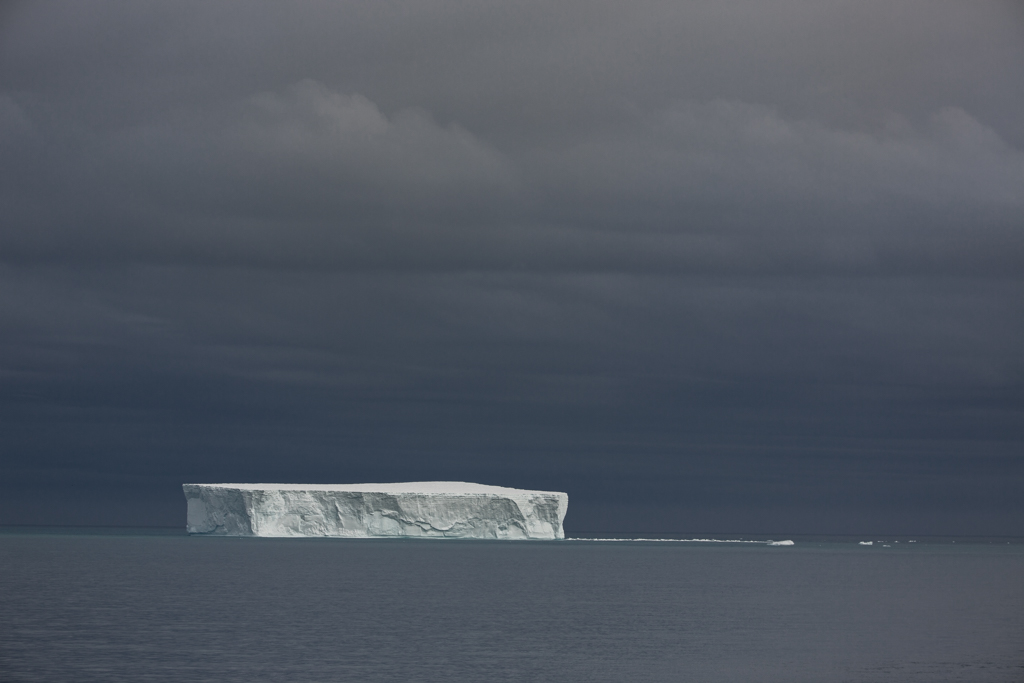 Huge iceberg with dark clouds
