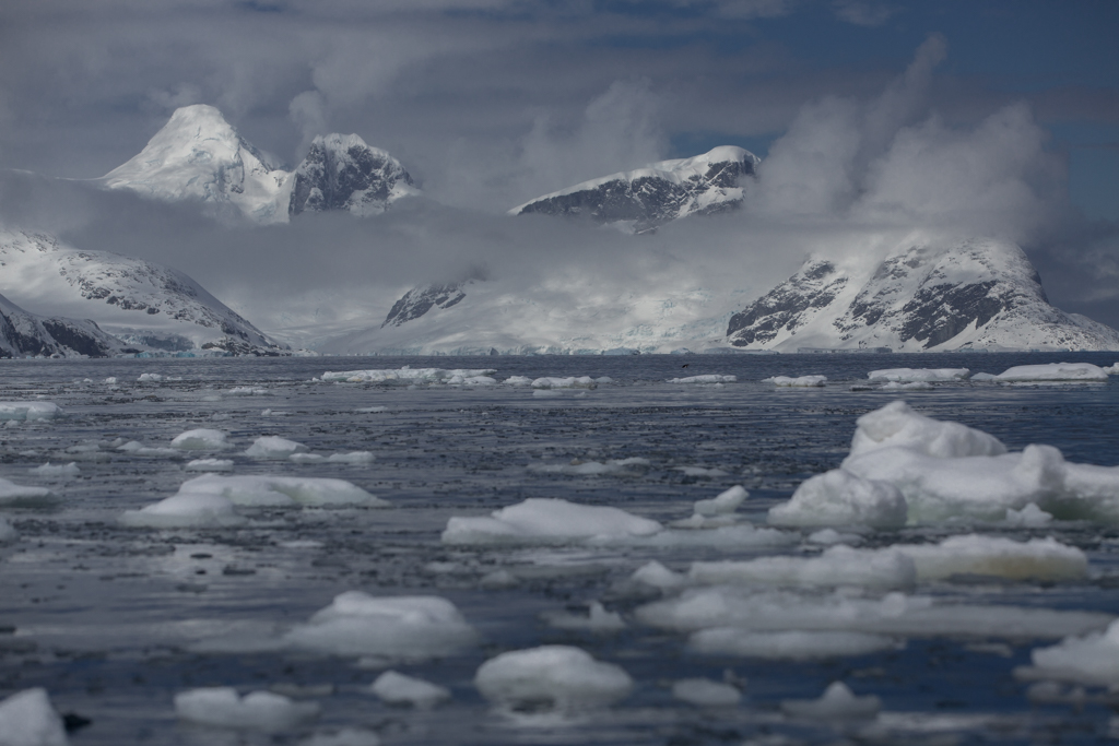 Clouds, ice floes and mountains in Pleneau Bay