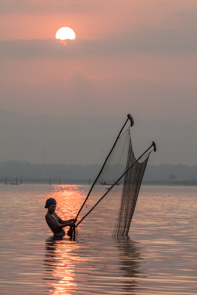 Fisherman with net at sunrise