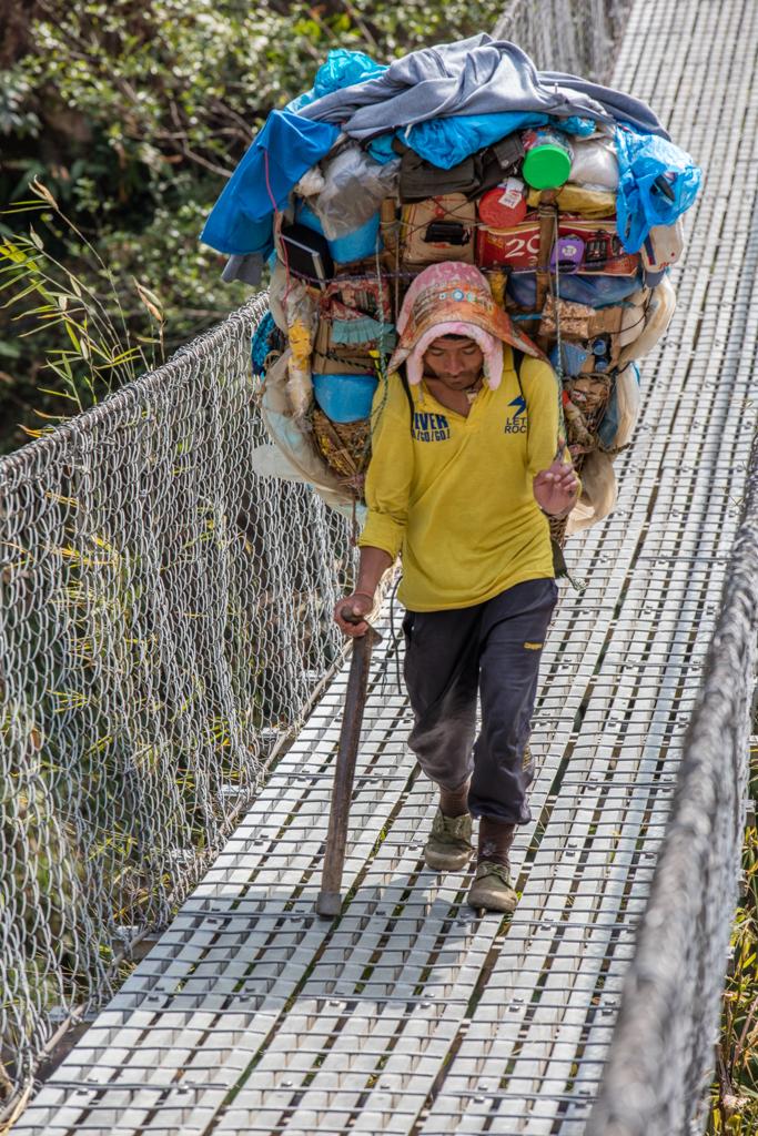 Nepalese porter on bridge