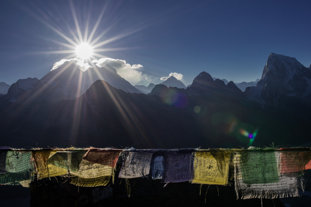 Prayer flags and sunstar at Mt. Everest
