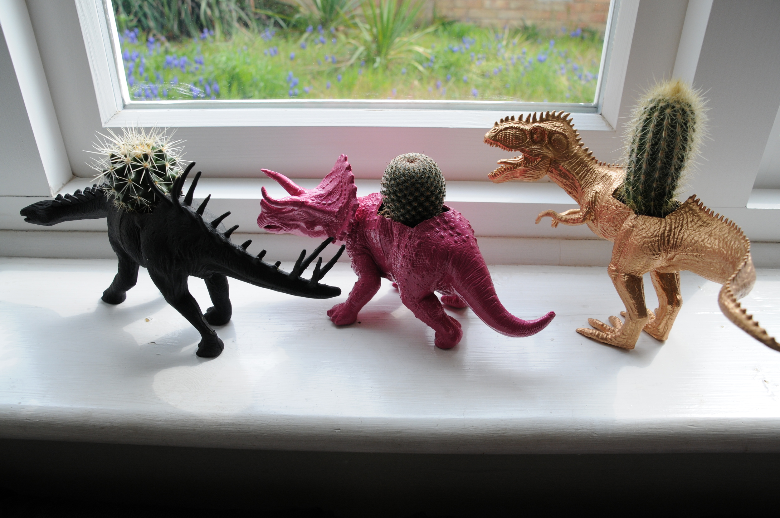 Black, pink and gold painted dinosaur planters
