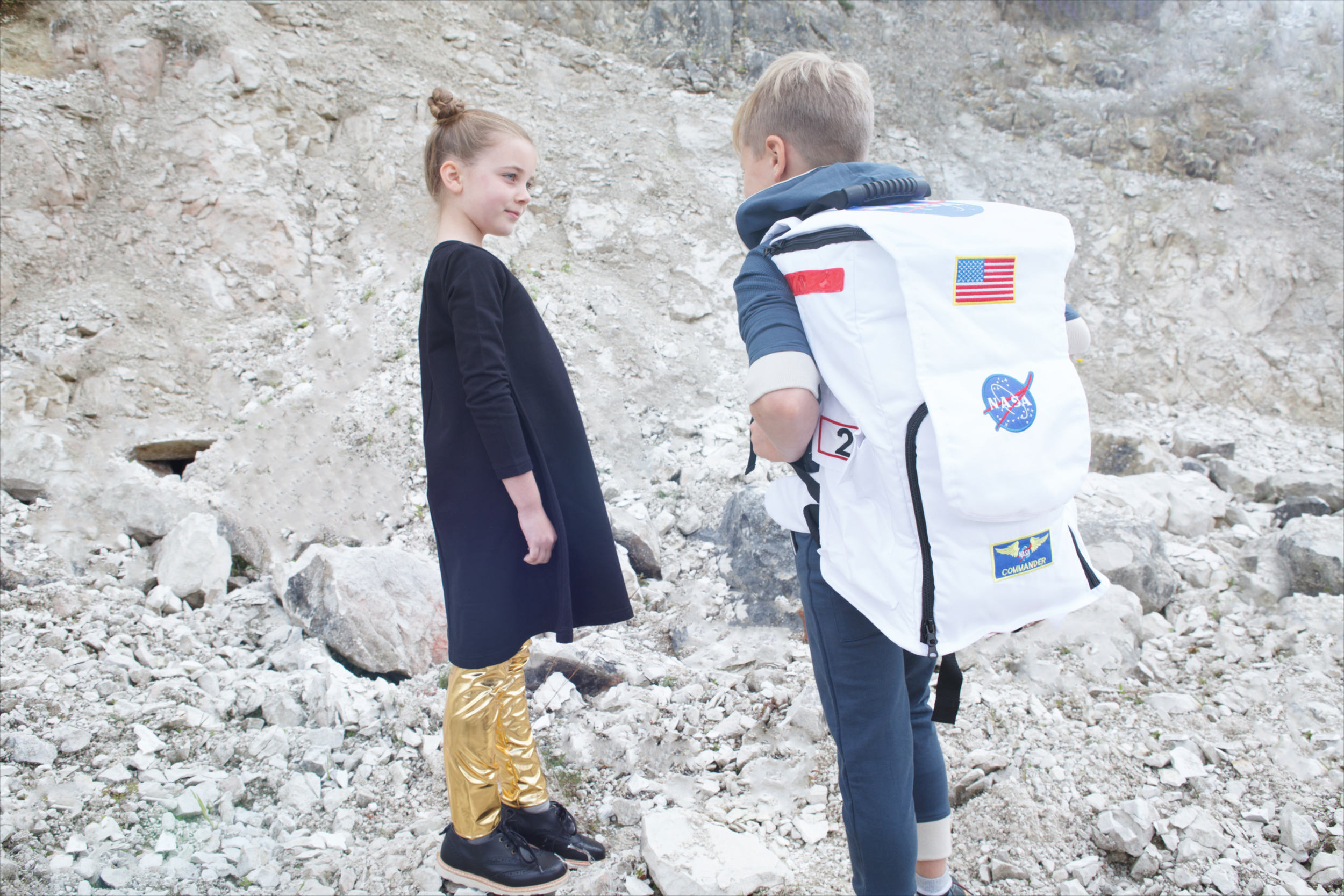 Sam: Blue all-in-one,  4funkyflavours . Cloud socks,  Bobo Choses . Blue monkey boots,  Young Soles . NASA backpack,  Spacekids.co.uk   Pippa: Black dress,  Mainio . Gold leggings,  Karen Brost . Black shoes,  Young Soles .