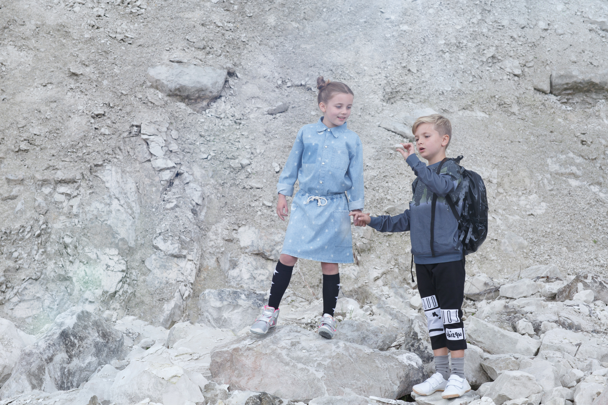 Pippa: Moon and stars denim shirt & skirt, Bobo Choses. Star socks, Molo. Silver trainers, Plae.  Sam: Space print sweatshirt, Someday Soon. Cropped trousers & backpack, Loud Apparel. Grey socks, Bobo Choses. White trainers, Plae.