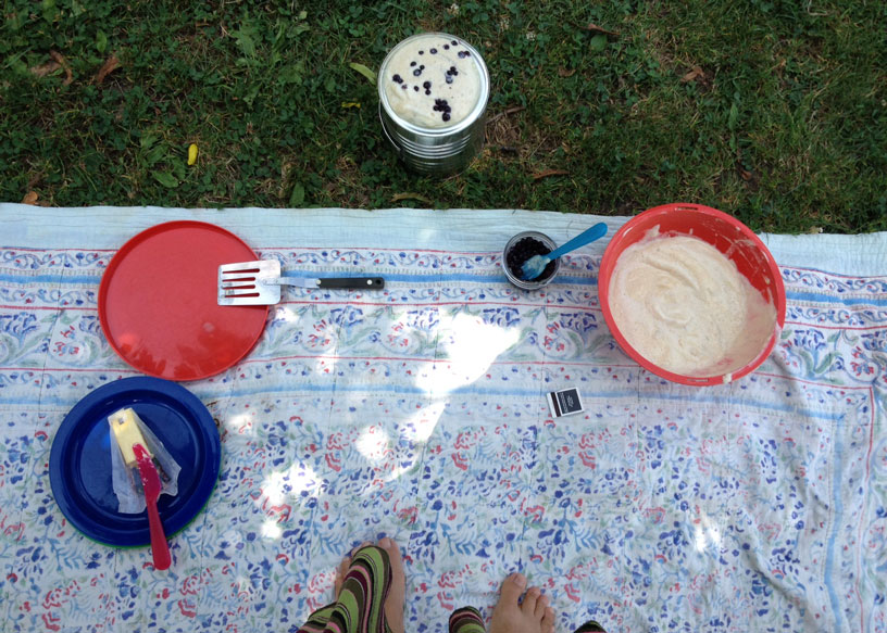 "pancake picnic; blueberry, buttermilk pancakes cooked on a "" buddy burner "" and served with butter and maple syrup; iced tea"