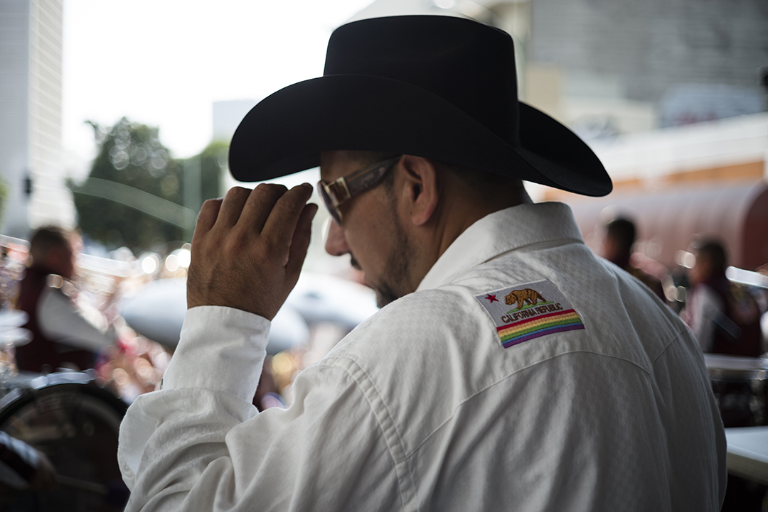 Host on the Latin stage with a California Pride patch.