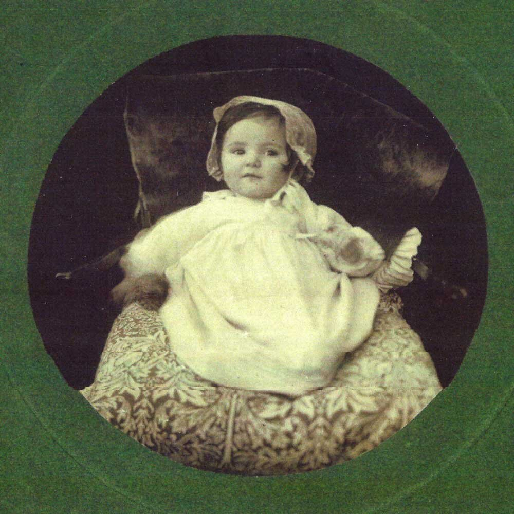 Baby Catherine Cockerell on a William Morris cushion