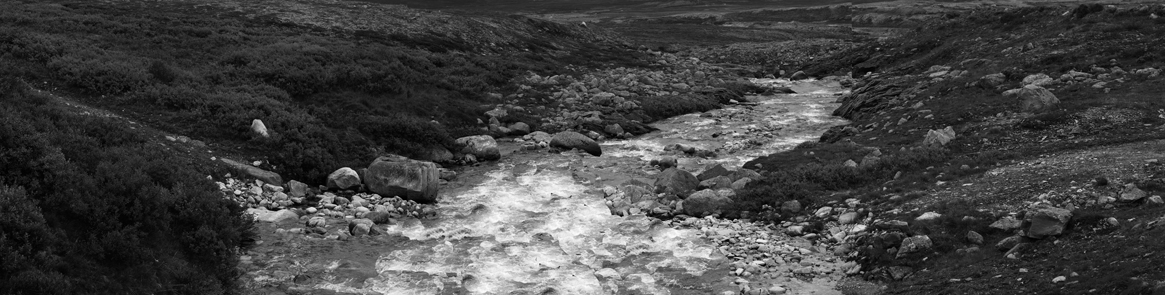 It looks like a road, but it can't be, because there is no bridge across the river. The road seems to cross it, but even now in summer when the stream is slow, there is no way of getting across the river. Obvious parallel tracks going down to the river on one side, and emerging again on the other shore remain. There might have been a bridge here at one time, but now there are no traces of such a construction, and the tracks clearly run all the way out into the water. They are wide and far apart from each other. It is as if a giant has marked the spot with an enormous stick, carving out two lines despite all natural formations.