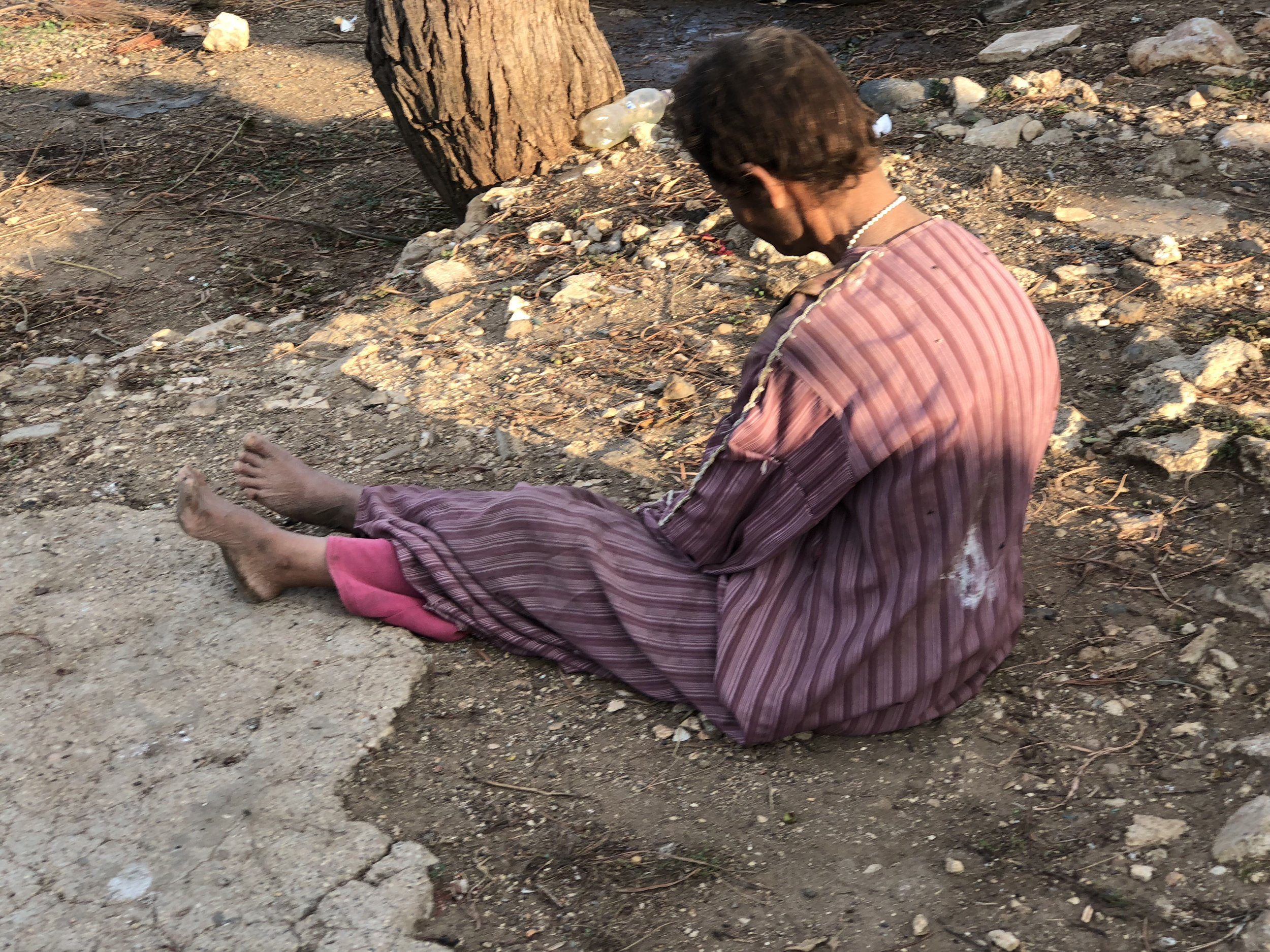 November 2017, Syria. A displaced woman, visited by Samara, with learning difficulties. She was barefoot and in tattered clothes, living in a tent-like structure in an informal settlement, having fled fighting in Aleppo. We provided boots, clothes and a dignity bag for her.