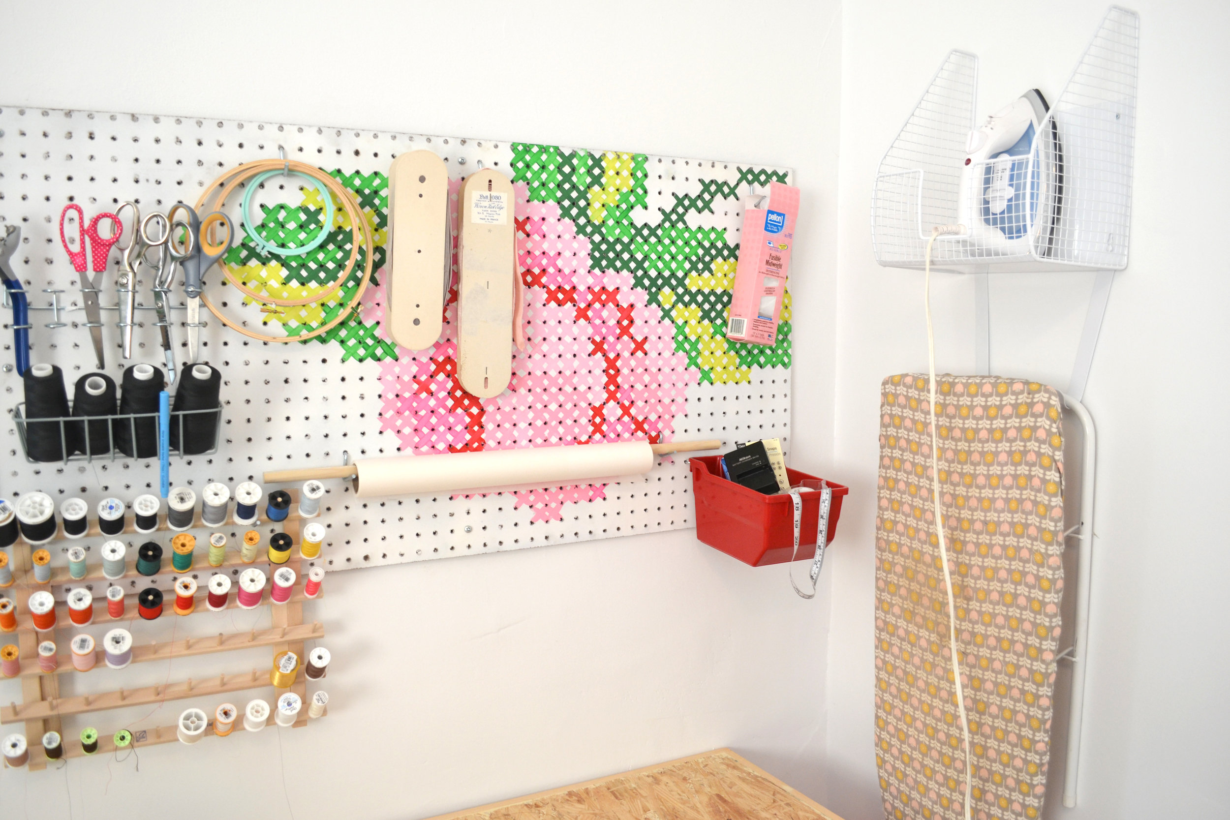 My peg board is a plain chip pegboard from Lowes that I spray painted white and used a cross stitch pattern to paint the rose. It wasn't receiving much utility in my old space, but I added a lot of features when I moved my space and now it's one of the things I am most thankful for. I also love having my little ironing board up and out of the way along with my iron.