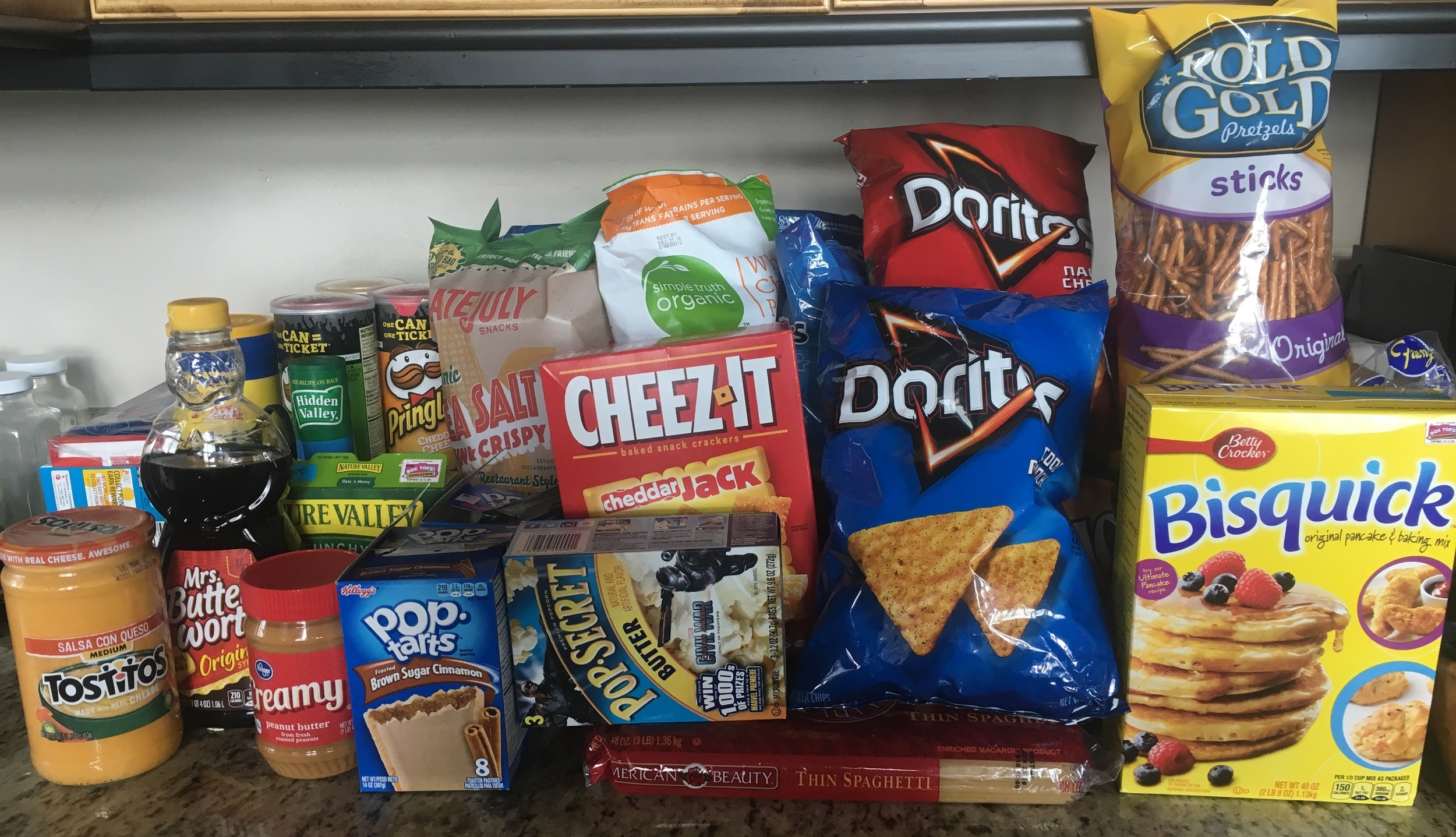"""Kitchen Counter -- Snack Pile. My two bags of """"organic"""" corn chips and popcorn peaking out amongst the others."""