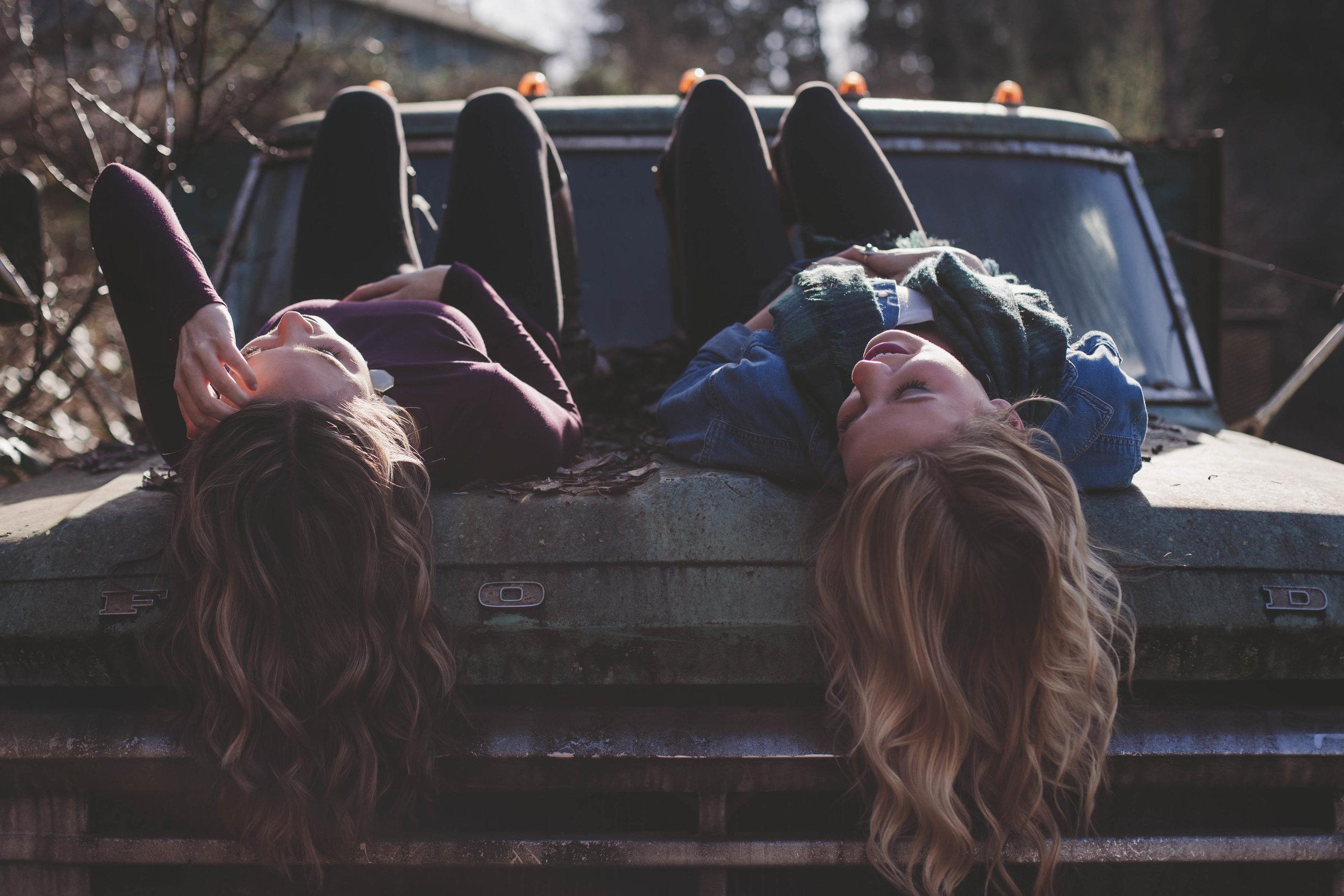 girls laying on back on hood of truck.jpeg
