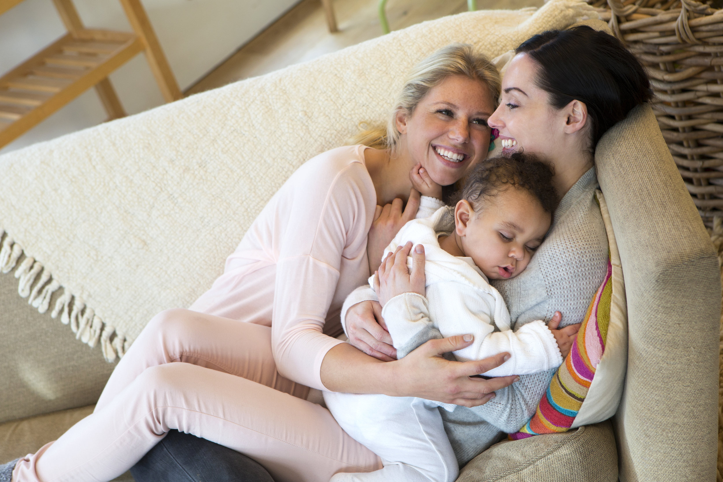 Same_sex_female_couple_cuddling_on_the_sofa_with_their_sleeping_son.jpeg