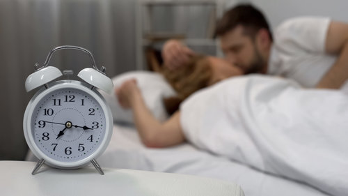 Happy_male_kissing_his_girlfriend_woken_up_with_alarm_clock_in_morning,_family.jpeg