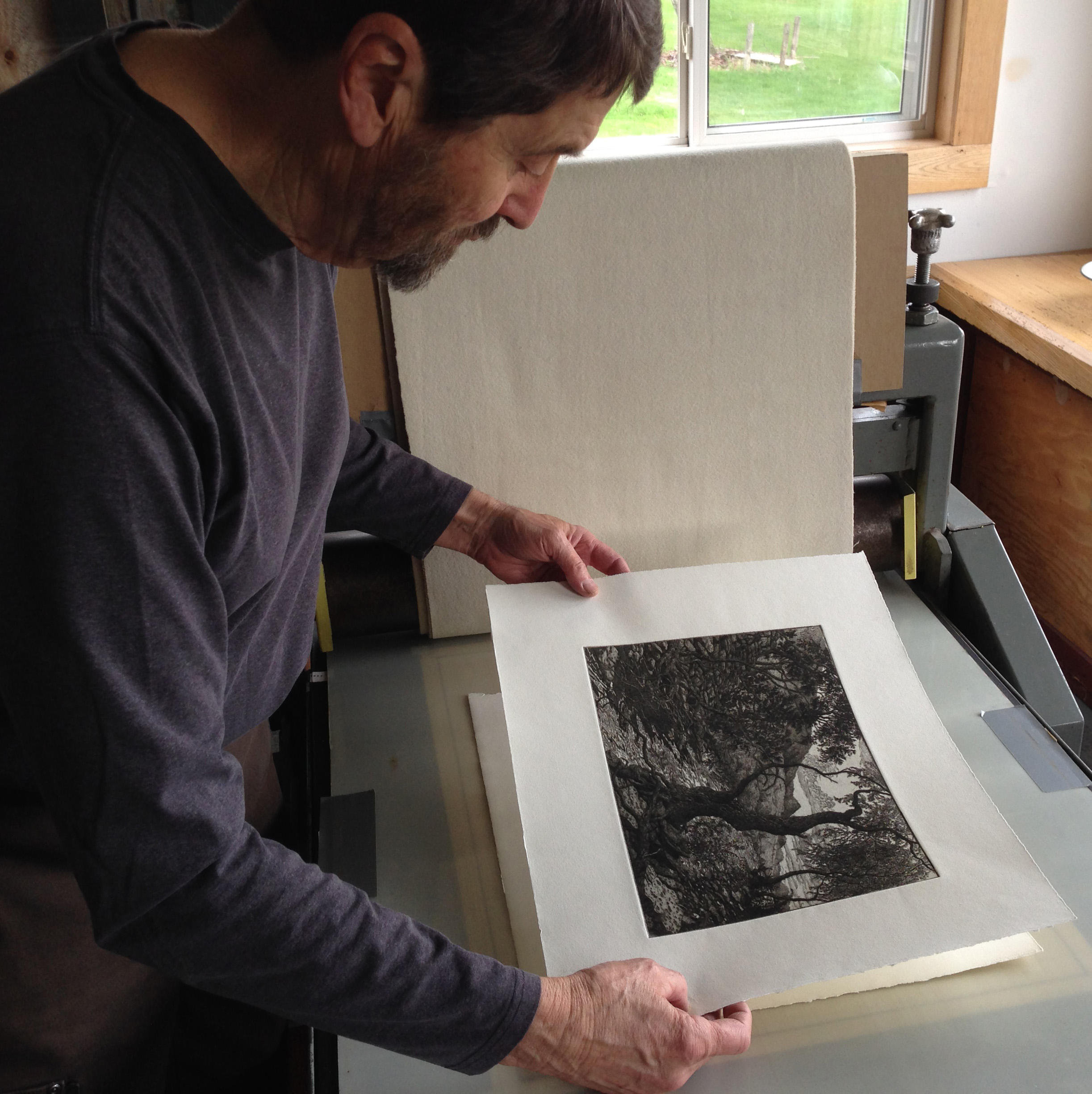"""Roger Bailey inspects one of the prints in the edition of """"The Dark Pool."""""""