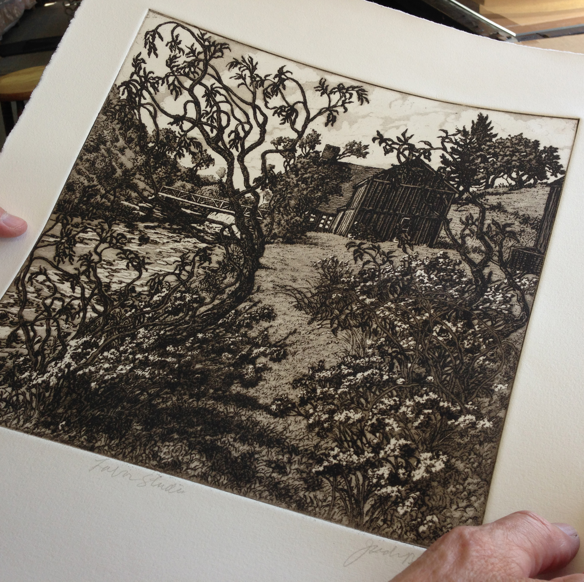"""Roger Bailey inspects a print to be sure it has not been over or under wiped. This was one of the more difficult prints in Jack's """"Experimental Suite"""" to ink and wipe with consistency."""