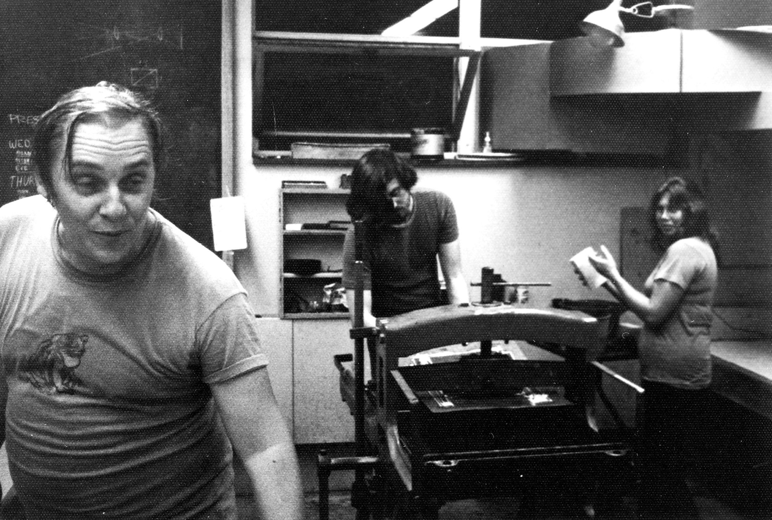 Jack examines prints, and Sondra assists printer Roger Bailey. It is  late July, 1973, in the print room at St. Lawrence University in Canton, New York.