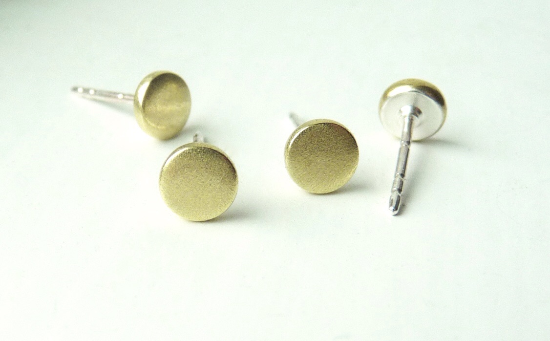 The backs are covered in silver. Enjoy brass without green ear lobes!