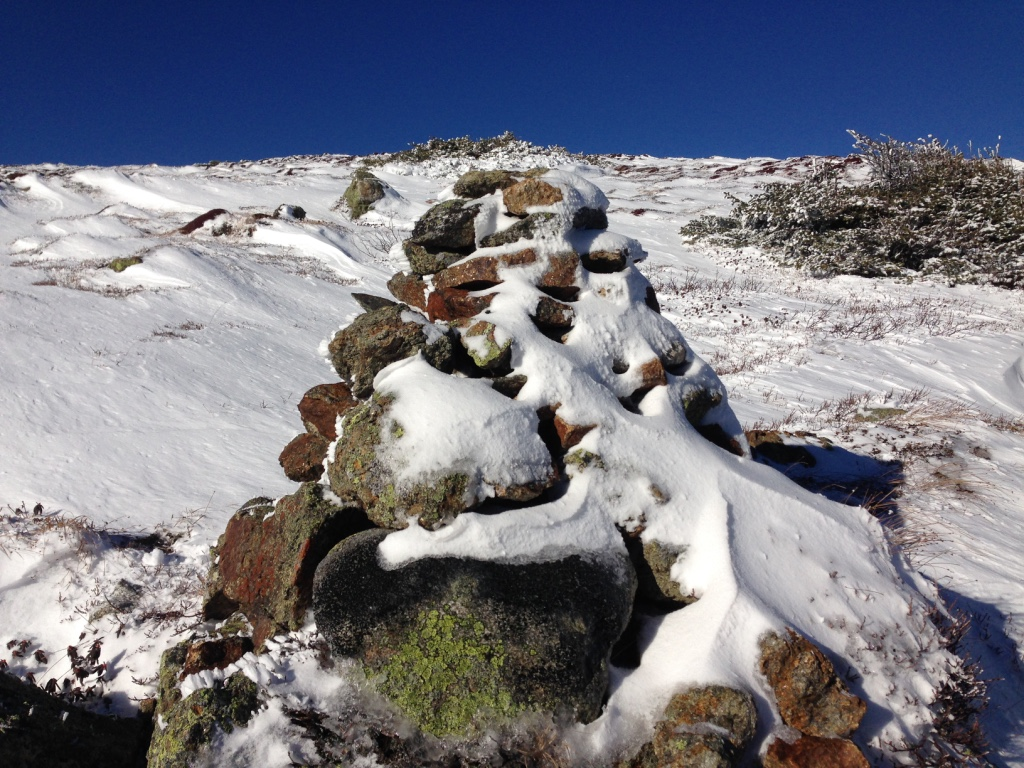 snow and lichen covered cairn leading me towards another summit