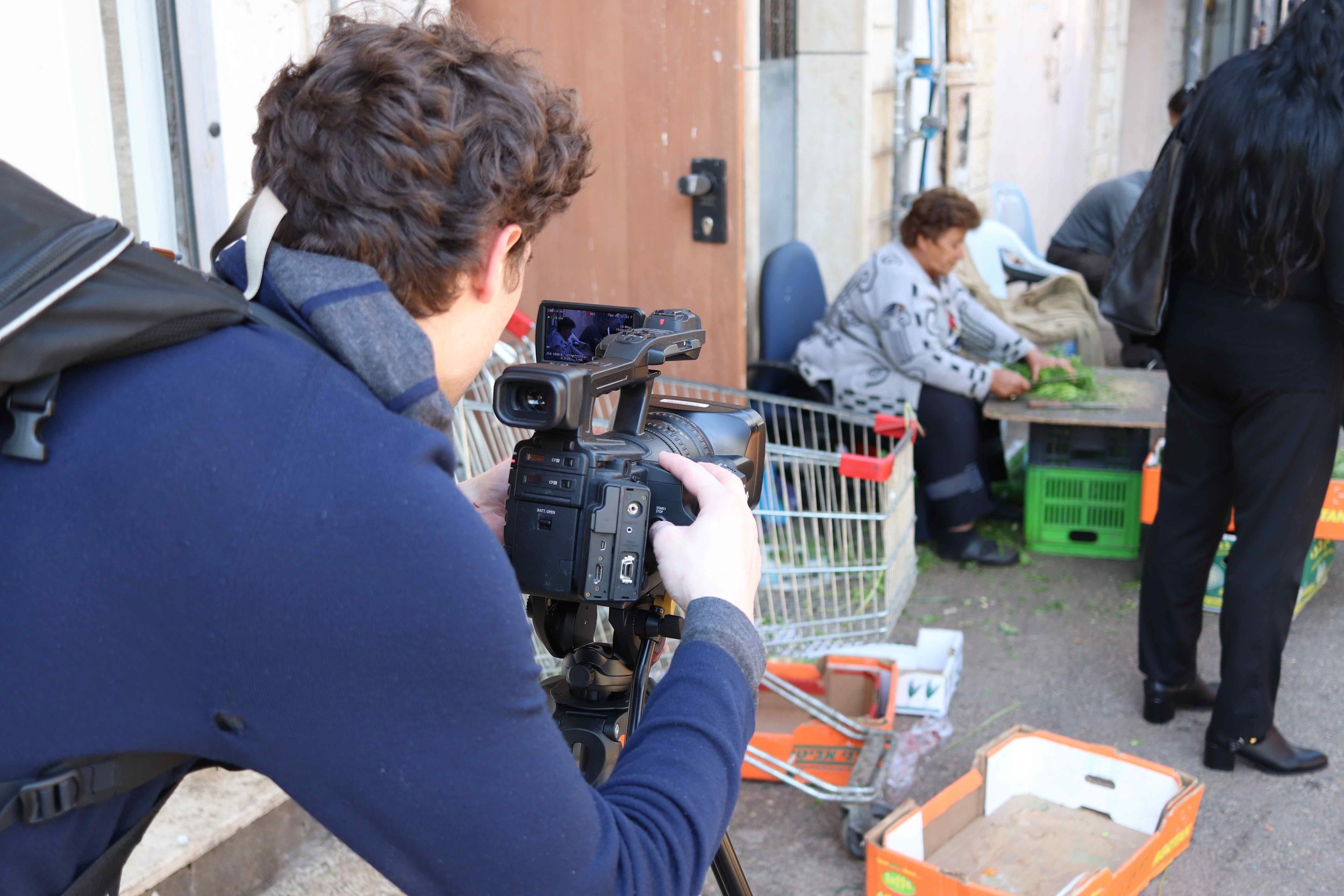 Newhouse broadcast student Tom Austen shoots video in the Haifa market.