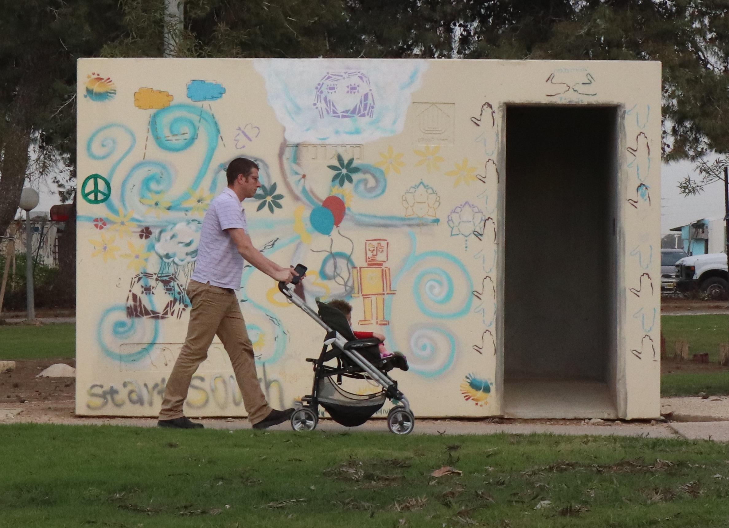 Man walks child past bomb shelter at Kibbutz Nahal Oz, on the border with Gaza.